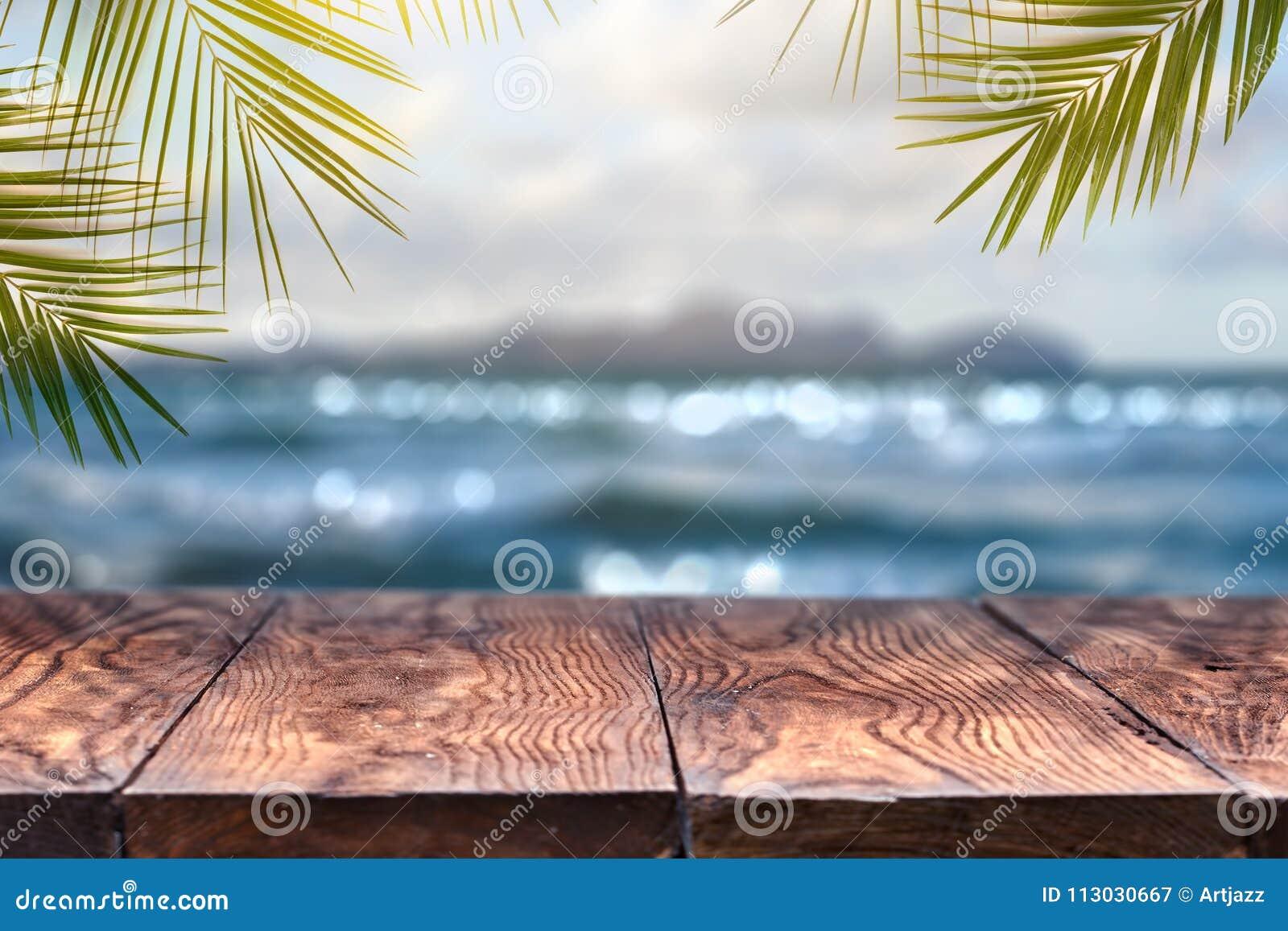 Vare el fondo borroso con el fondo de las hojas de palma con la tabla de madera vieja del vintage