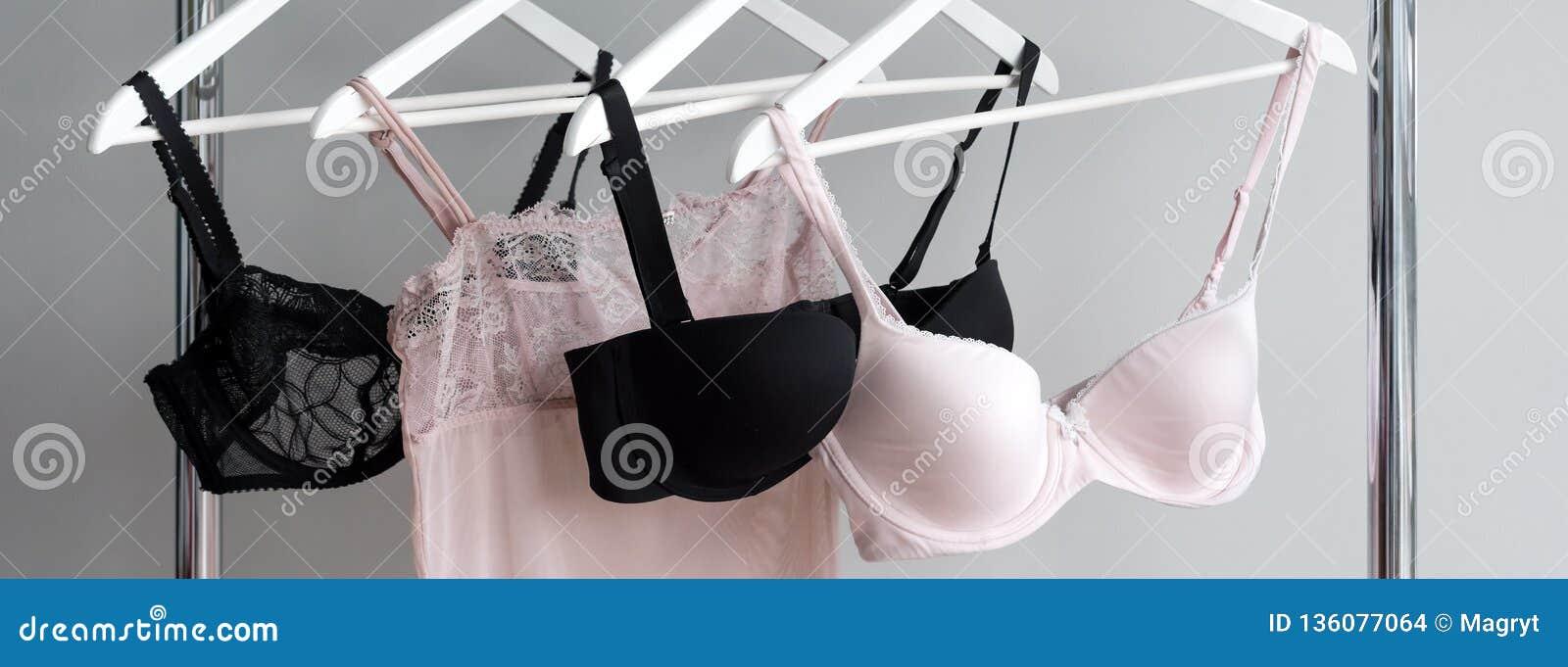 Vareity del sujetador que cuelga en una suspensión Materia textil, ropa interior Sujetador femenino en tienda de la ropa interior