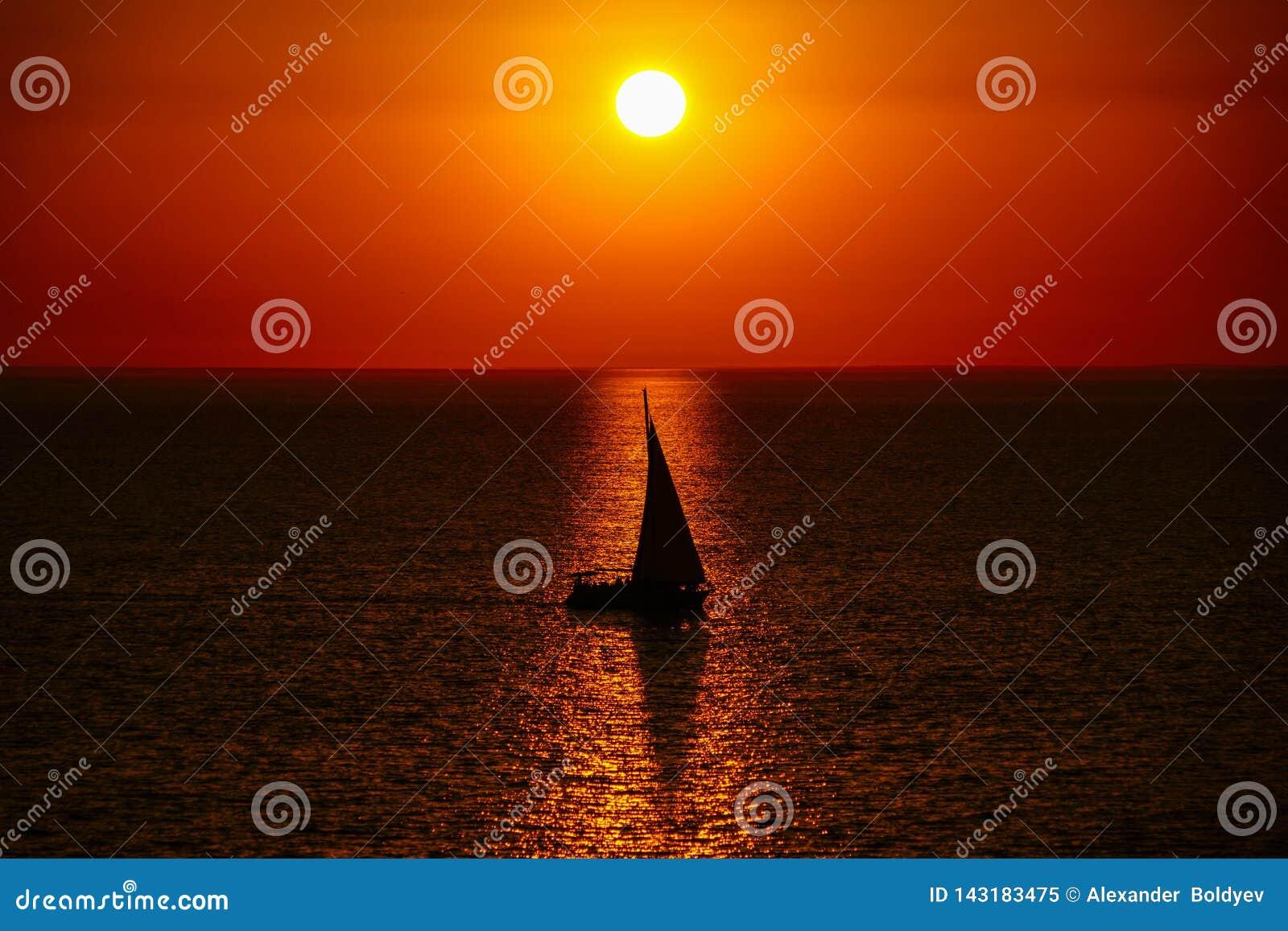 Varend jacht in de zonsondergang, de schaduw van de zeilboot op de achtergrond van de Gouden zonsondergang en bezinning in