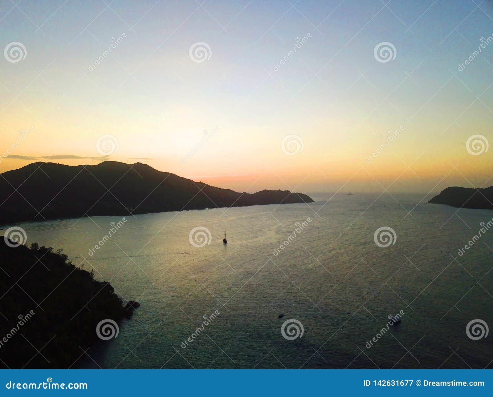 Varend schip en een zonsondergang in de Seychellen