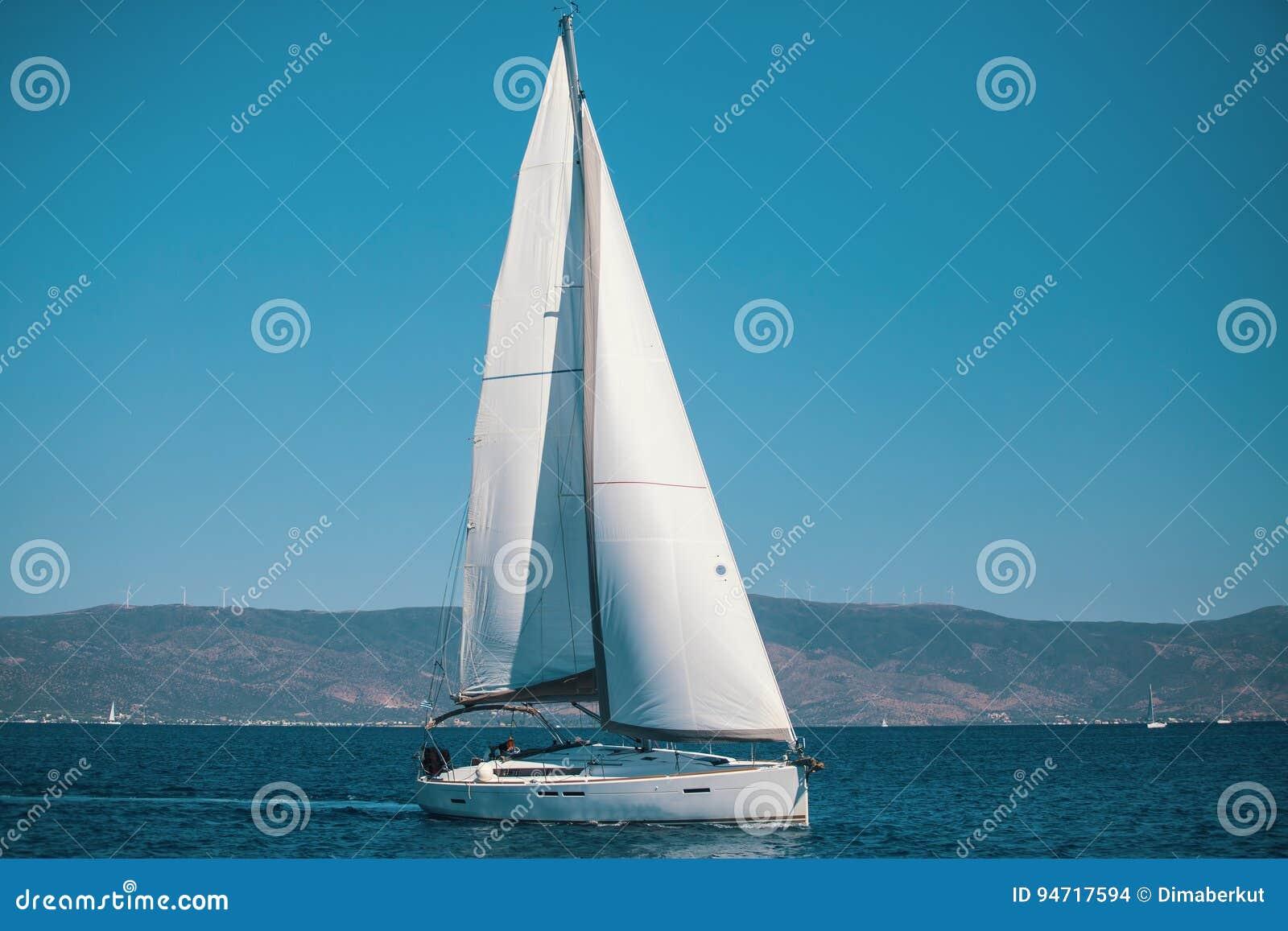 Varend schipjacht met witte zeilen in het Egeïsche Overzees