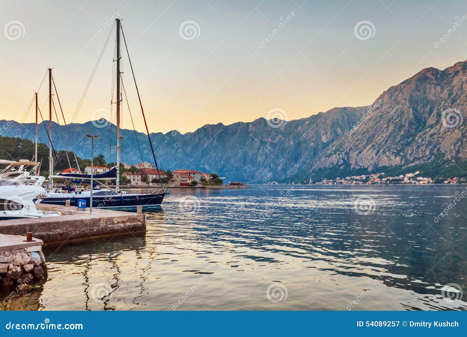Varende boten in jachthaven bij zonsondergang