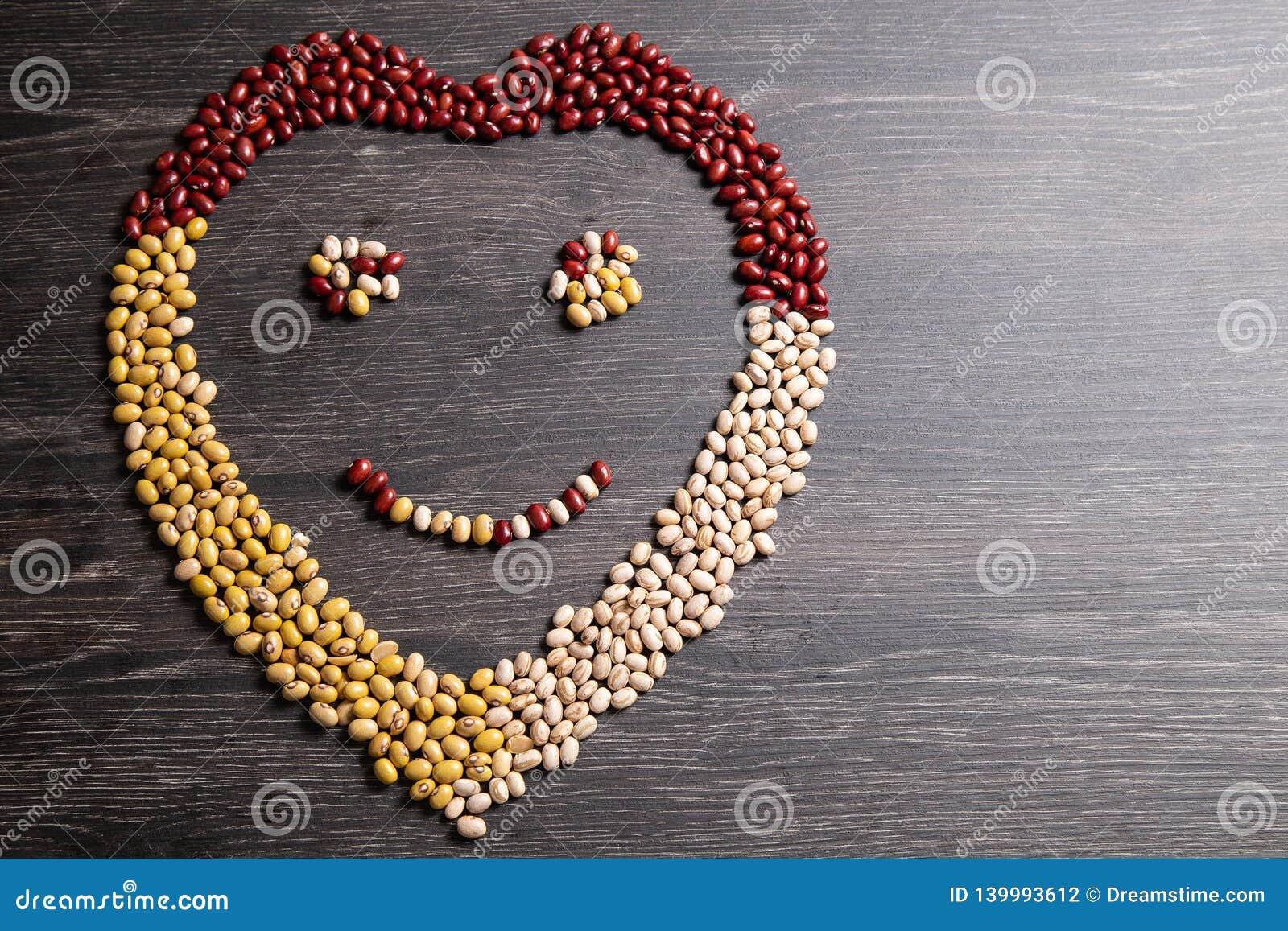 Variété de haricots sur la cuillère en bois sur le fond en bois fèves de mung, arachides, haricots rouges et haricots bruns