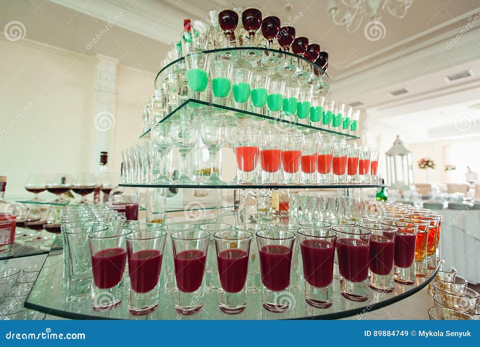 Variété de tirs jaunes et rouges verts colorés d alcool en petits verres se tenant dans la rangée sur un support en verre