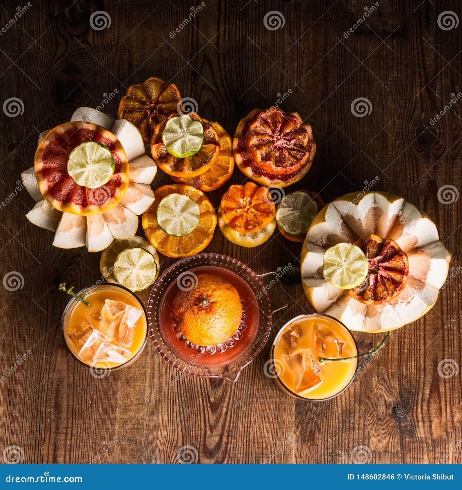 Vari agrumi variopinti con il succo di agrumi schiacciato fresco in vetri con i cubetti di ghiaccio sulla tavola con gli ingredie