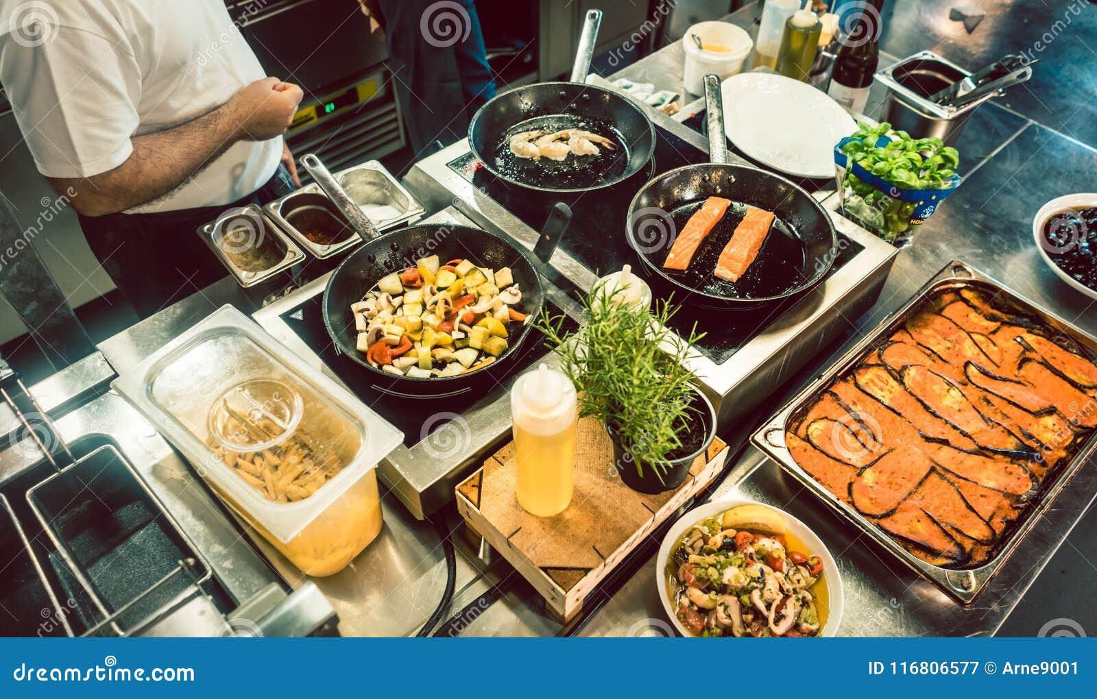 Vari ingredienti freschi sulla stufa di una cucina commerciale