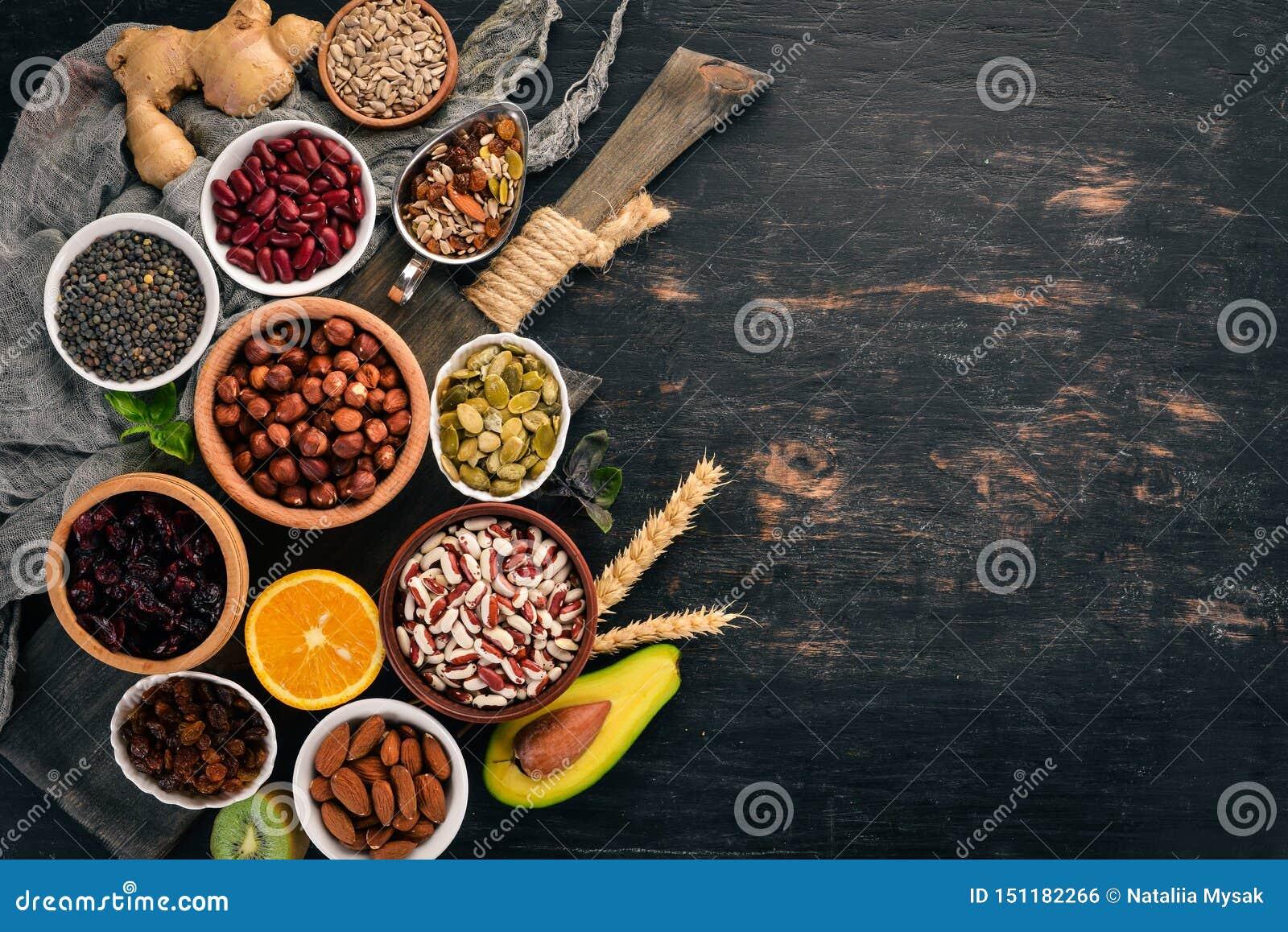 Vari superfoods Frutti, dadi, fagioli, frutta e verdure secchi Su un fondo di legno nero