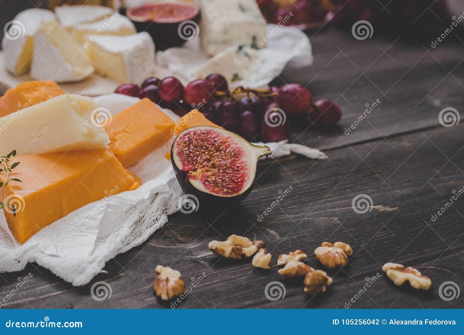 Vari tipi di formaggio con i frutti e di dadi sulla tavola scura di legno Fuoco selettivo