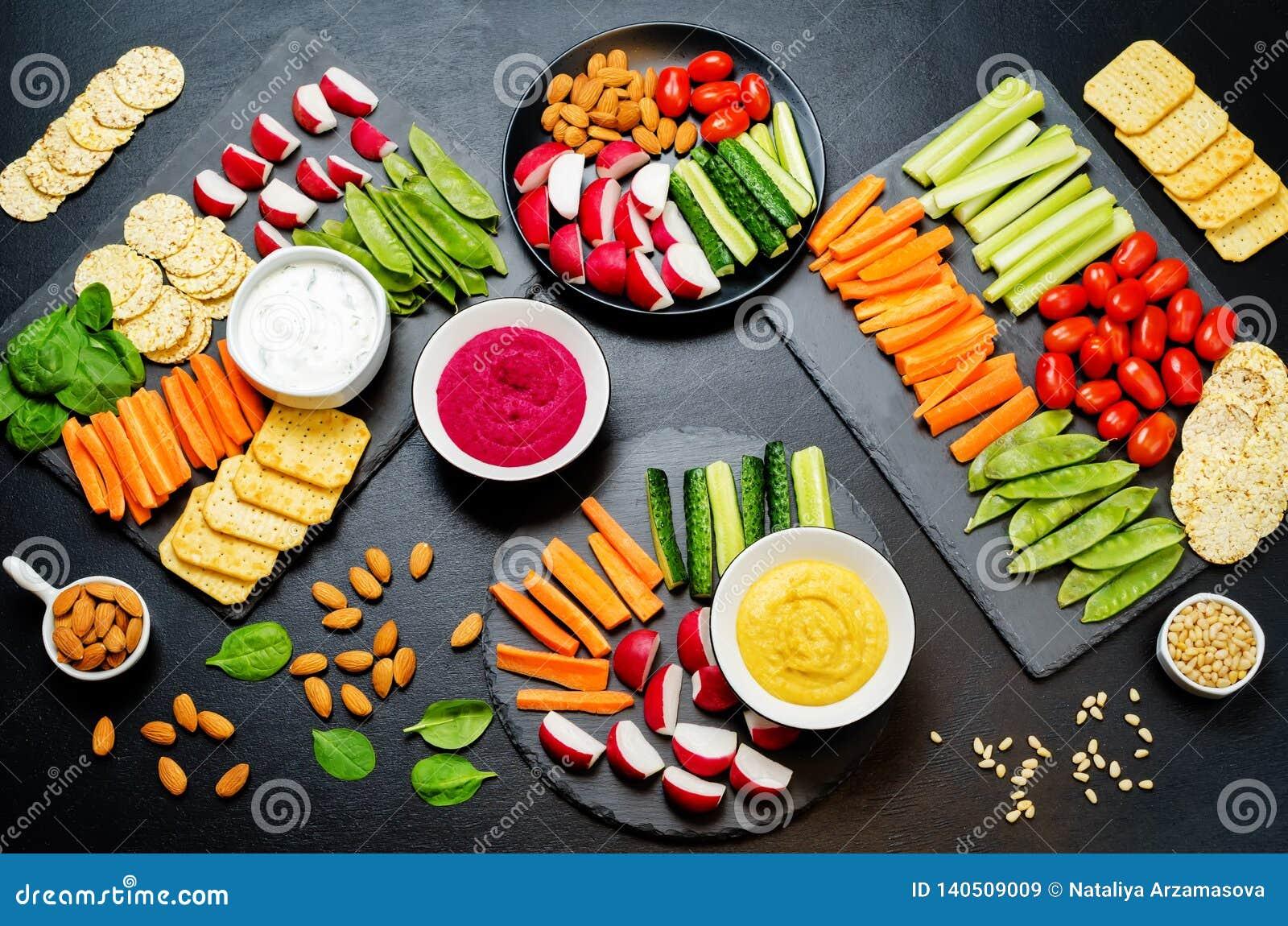 Variatie van gezonde veganistsnacks Groenten, crackers, onderdompeling en hummus