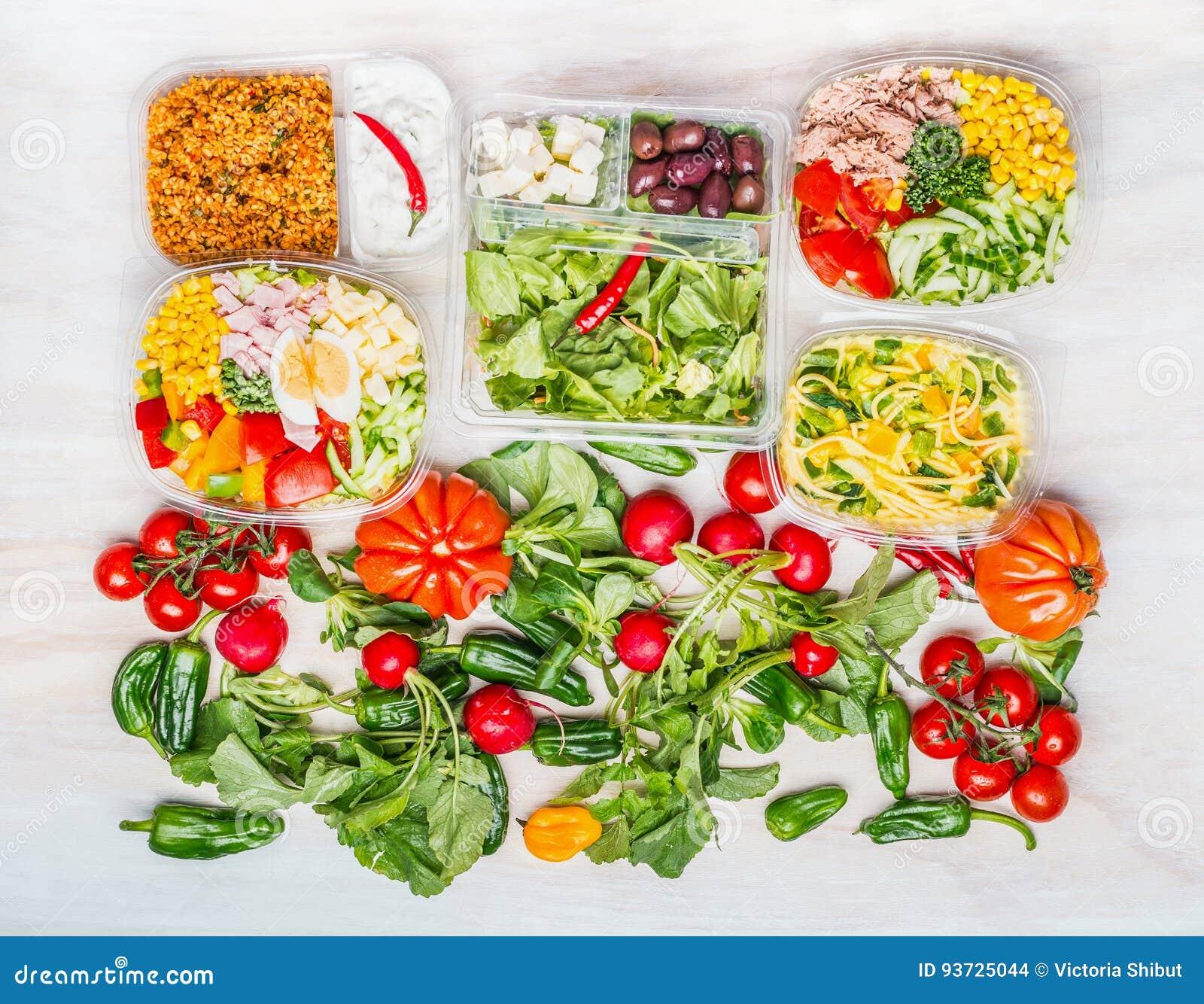 Variation av sunda sallader i lunchaskar med vit träbakgrund för ingredienser