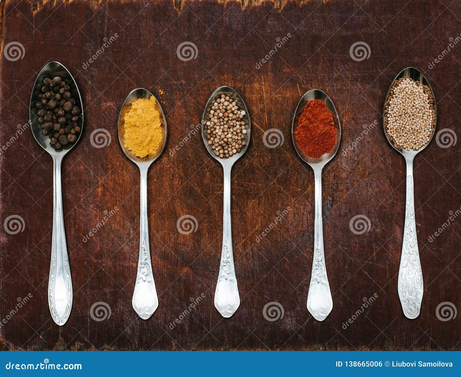 Varie erbe e spezie Colourful per la cottura sul fondo scuro Le erbe e le spezie su un fondo di legno