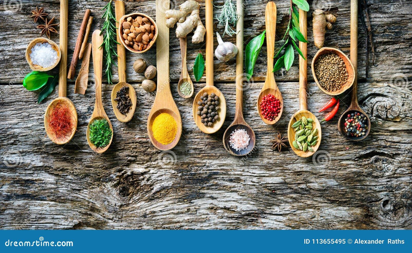 Varie erbe e spezie per la cottura sul bordo di legno anziano