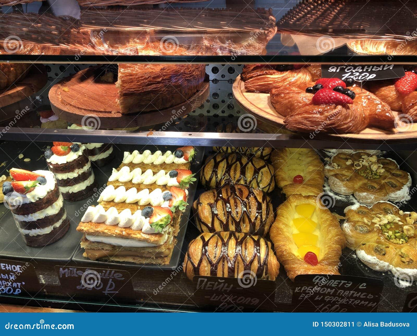 Variedad de postres deliciosos altos en calorías que mienten en la ventana de la panadería
