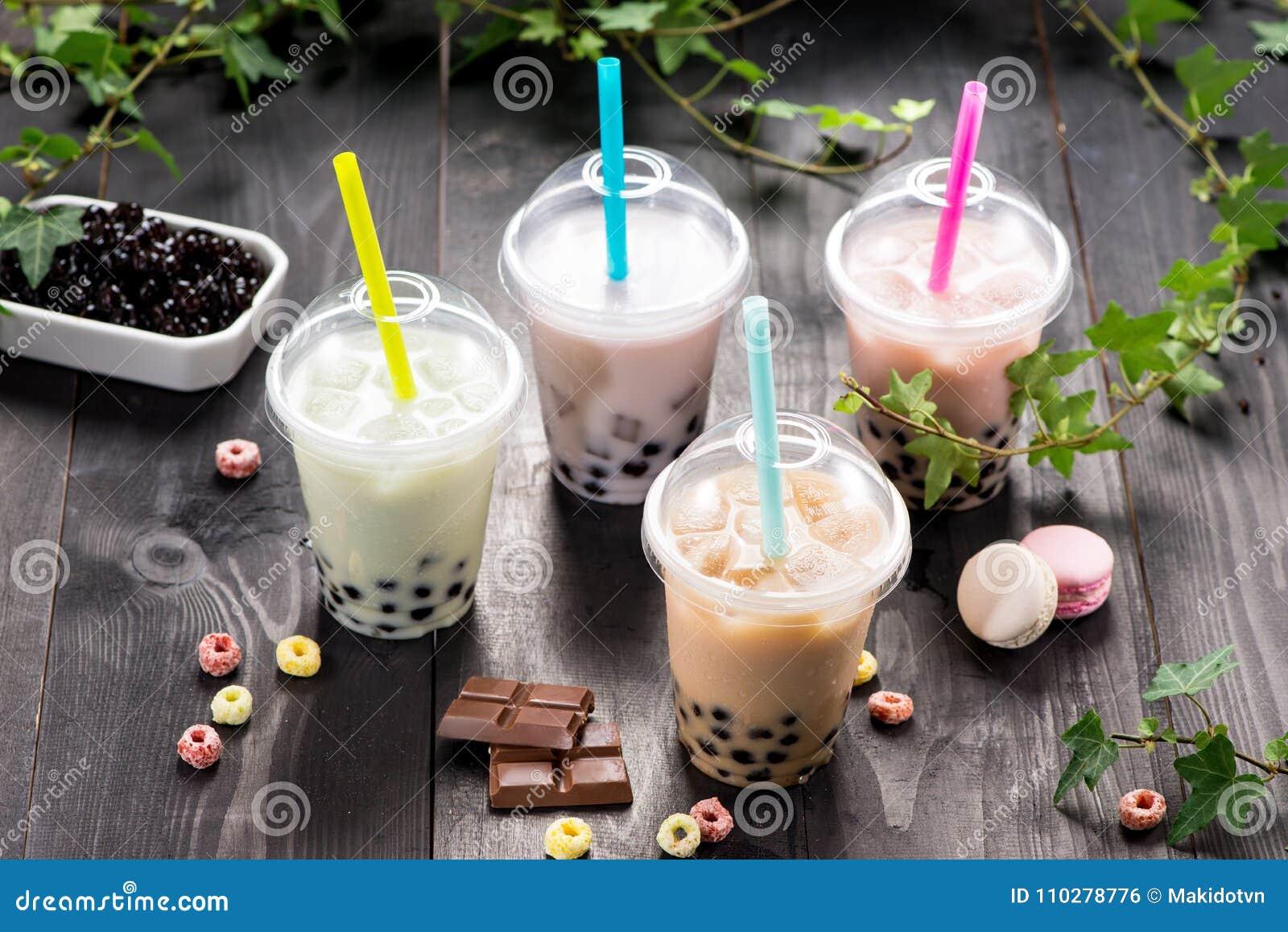 Variedad de té de la burbuja en tazas plásticas con la paja en TA de madera