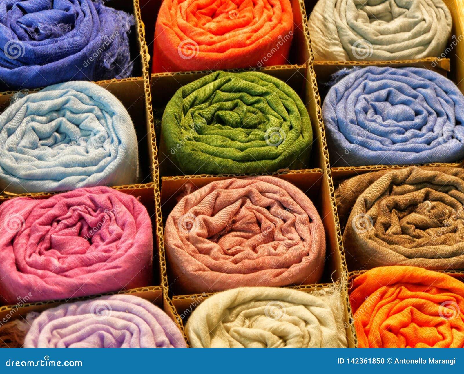 Variedade de scarves de seda rolados de cores vívidas diferentes