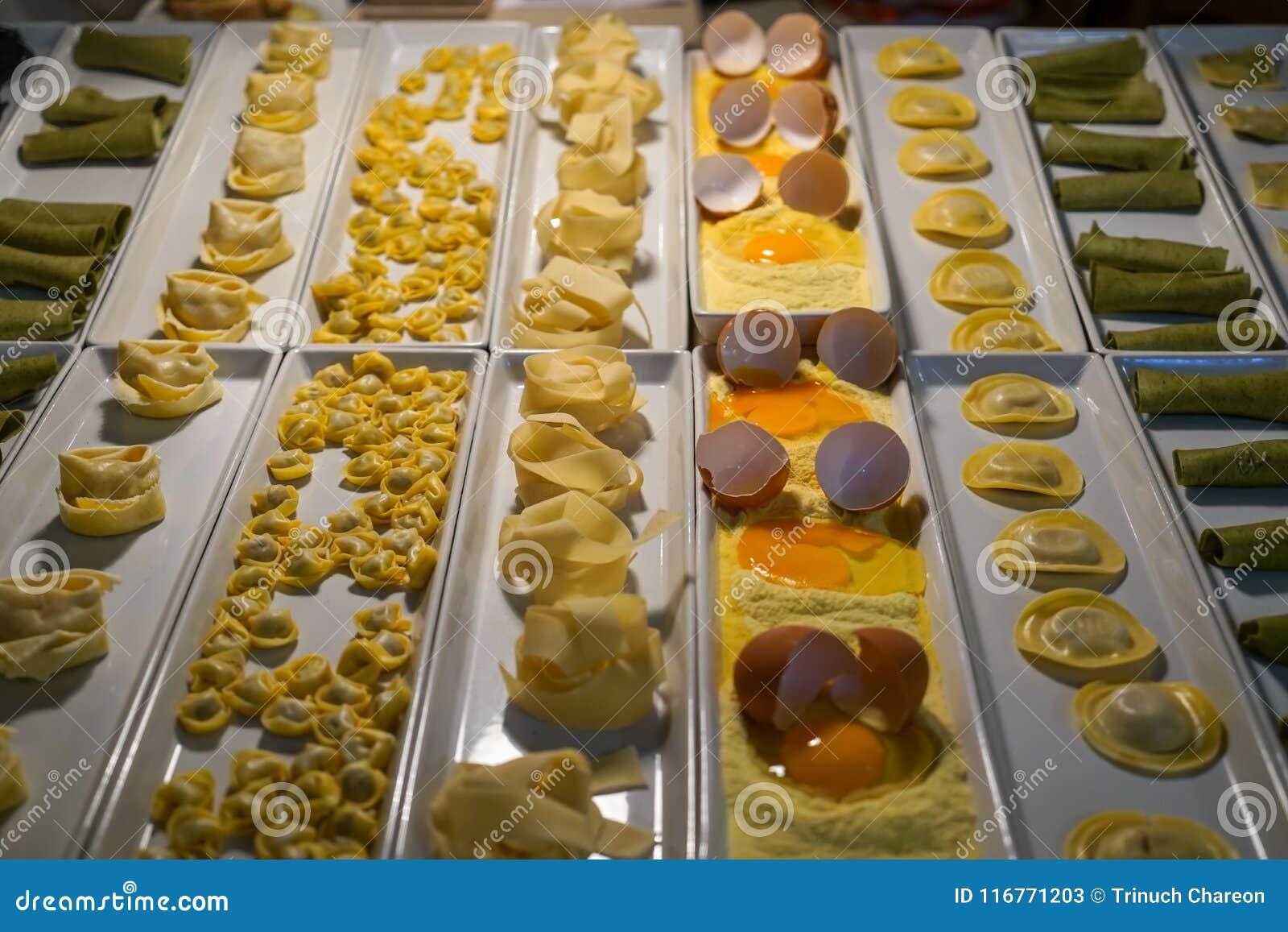 Variedade de tipos frescos mostra da massa para o jantar que inclui o pappardelle, o ravioli, etc. na placa branca do retângulo n
