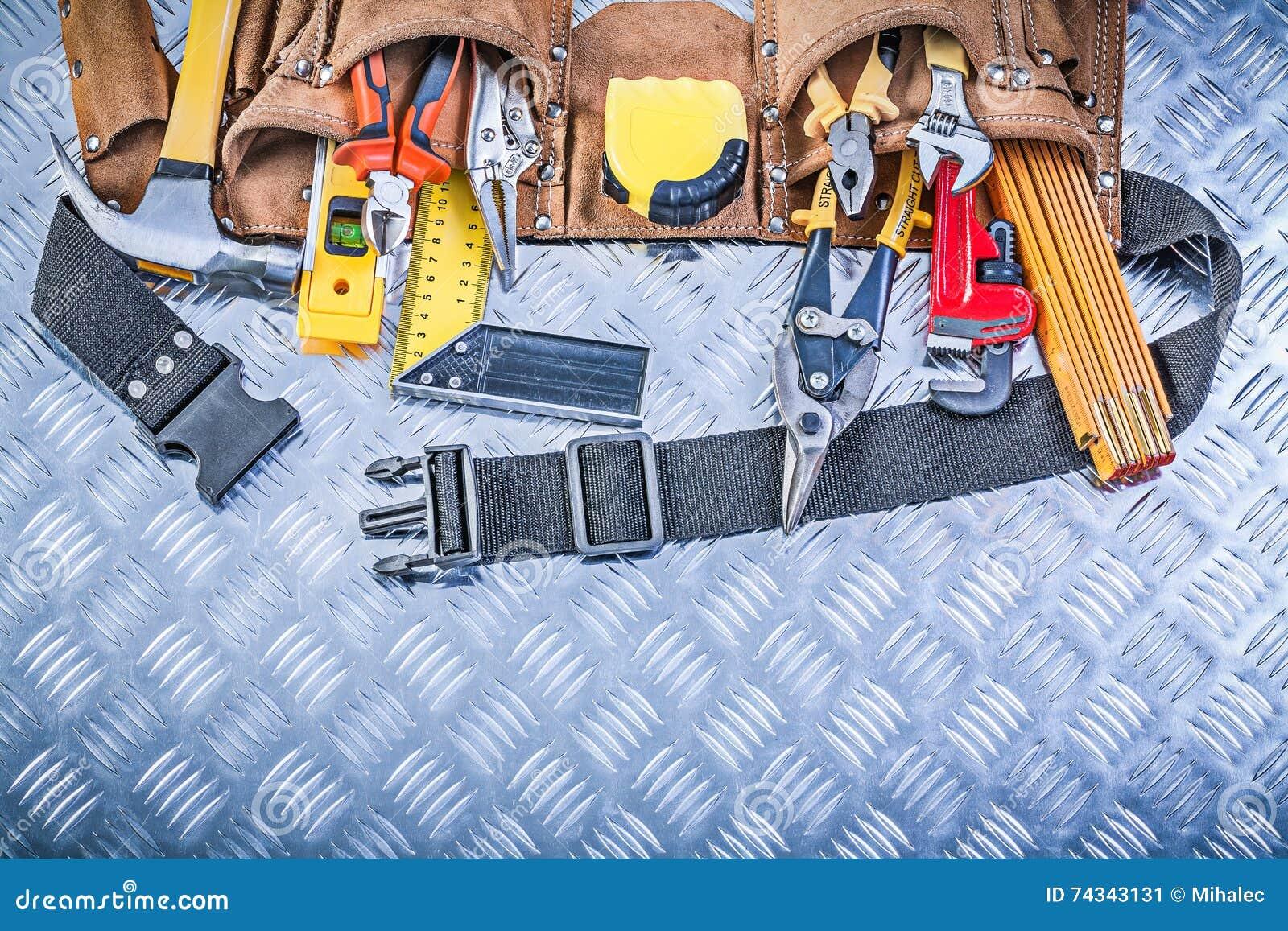 Variedade do trabalho feito com ferramentas da construção na correia de couro da construção em c