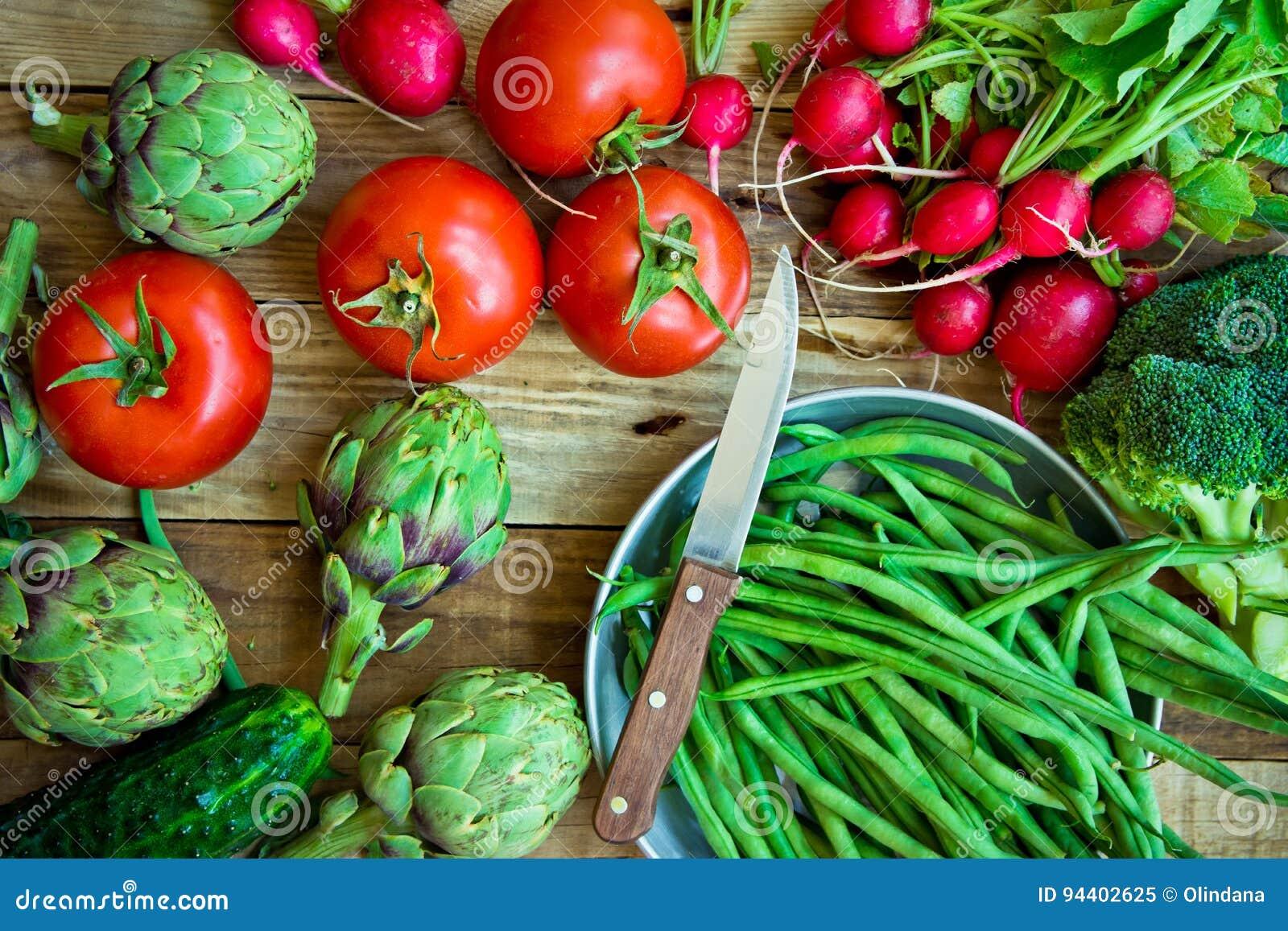 Varietà di fagiolini organici variopinti freschi delle verdure, pomodori, ravanello rosso, carciofi, cetrioli sul tavolo da cucin