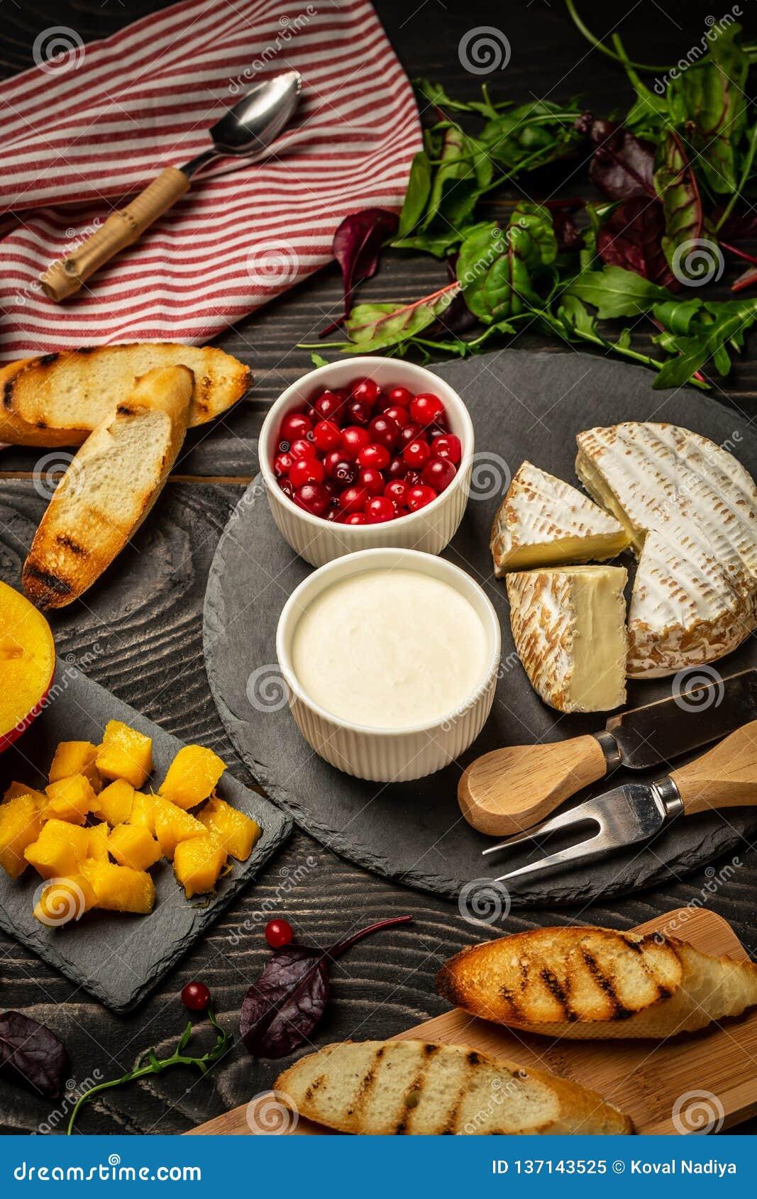 Varietà di ingredienti alimentari freschi per i panini dolci di crostini della bacca con il mirtillo rosso del mango di ricotta,