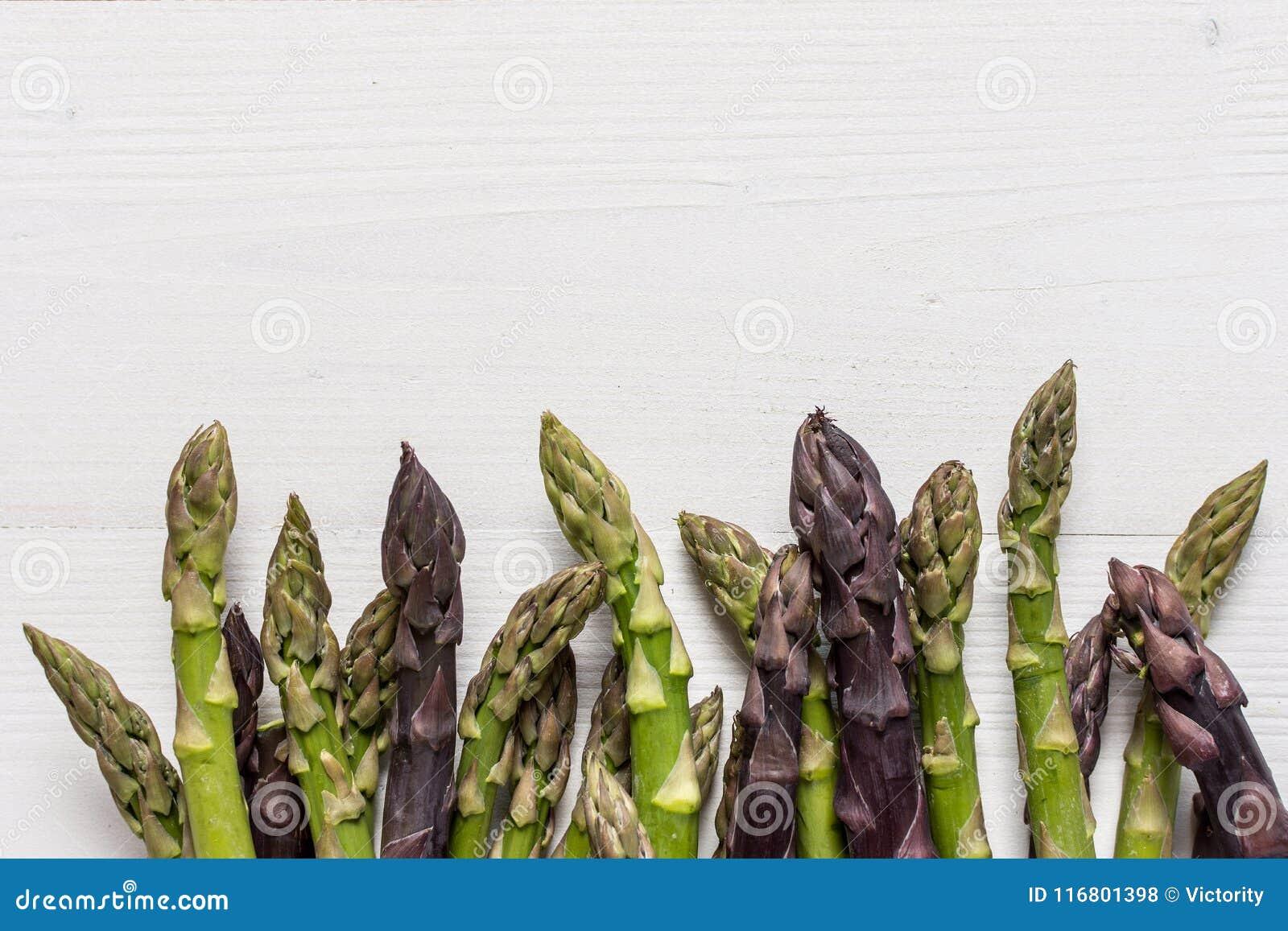 Varietà fresche dell asparago su fondo di legno bianco