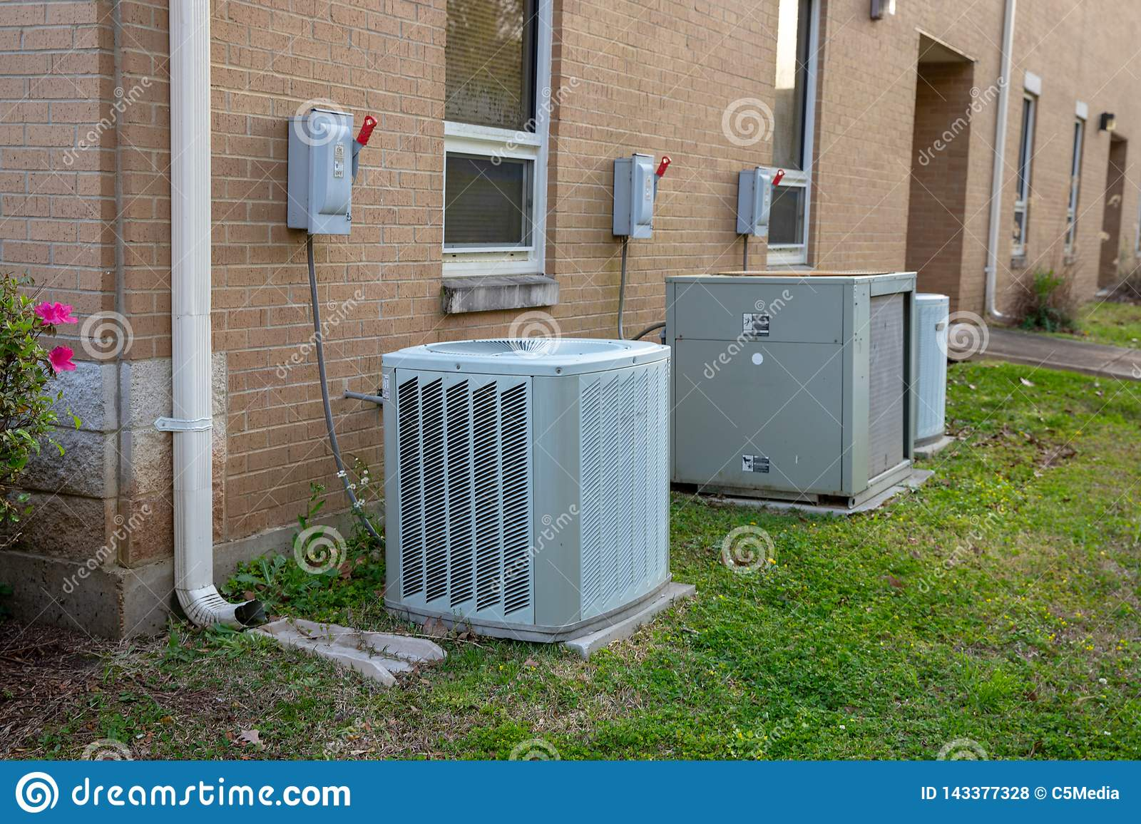 Variety of air conditioner units outside of commerical building
