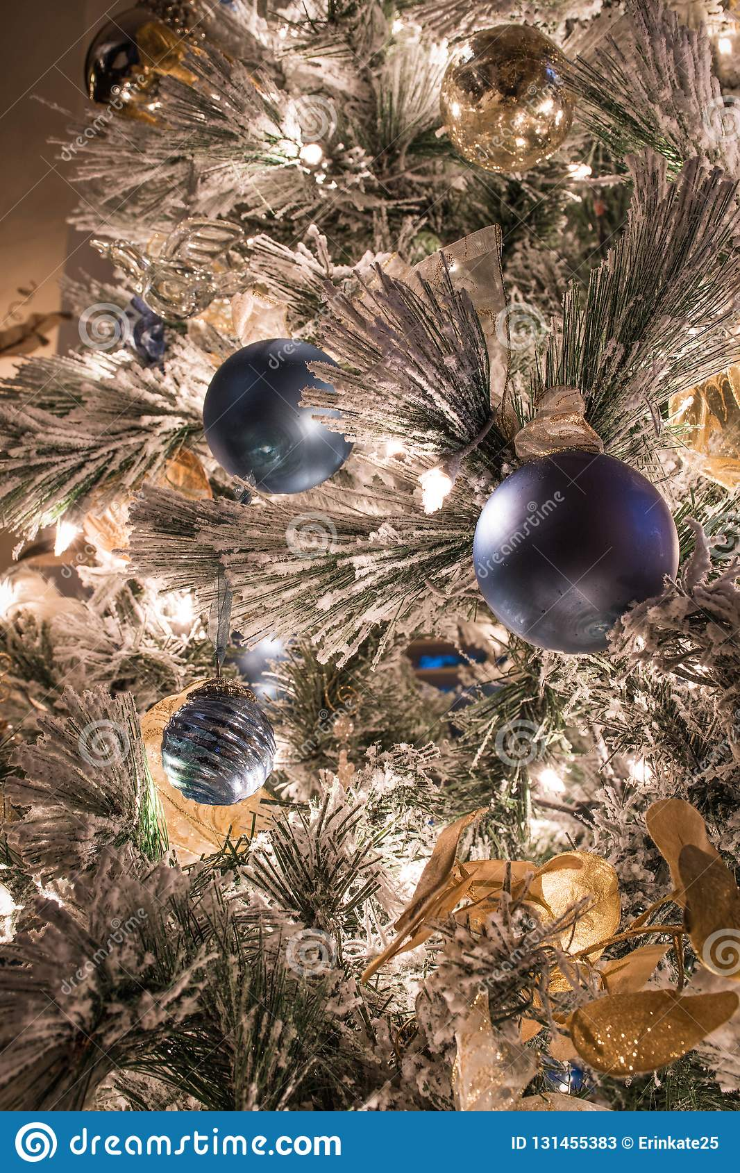 A Variety Of Blue And Gold Christmas Ornaments On A Flocked Christmas Tree Stock Image Image Of Decoration Ball 131455383