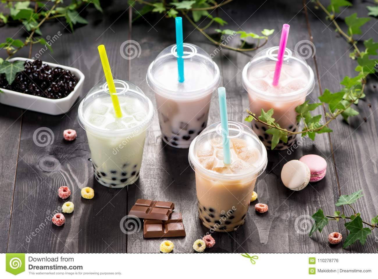 Variety of bubble tea in plastic cups with straws on a wooden ta