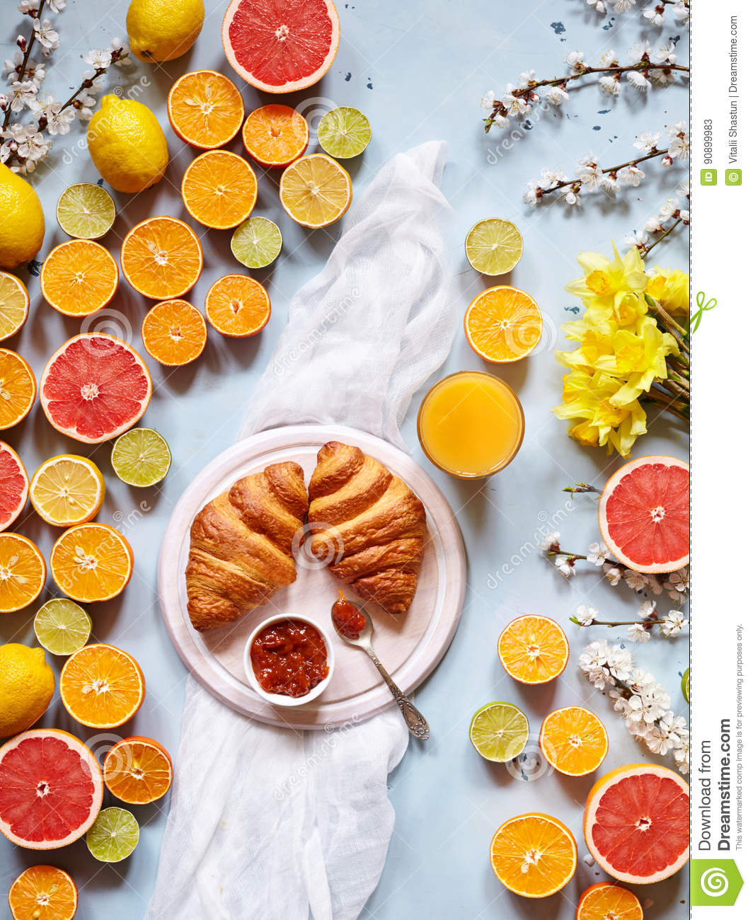 Variety of fresh citrus fruits for making juice or smoothie with fresh croissants and juice on a light blue background