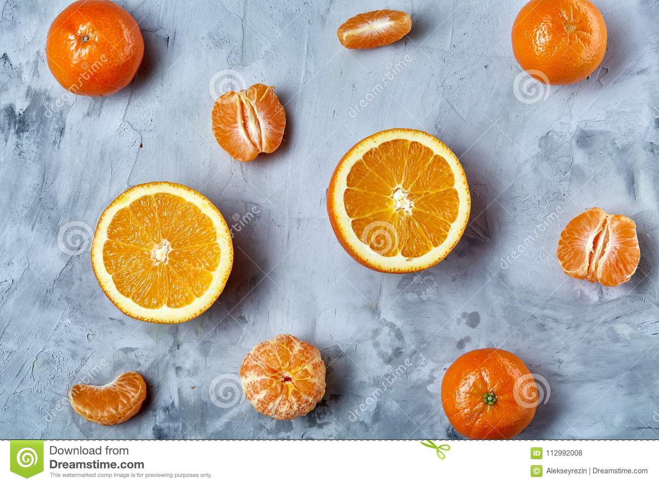 Variety of fresh citrus fruits for making juice or smoothie over light textured background, top view, selective focus.