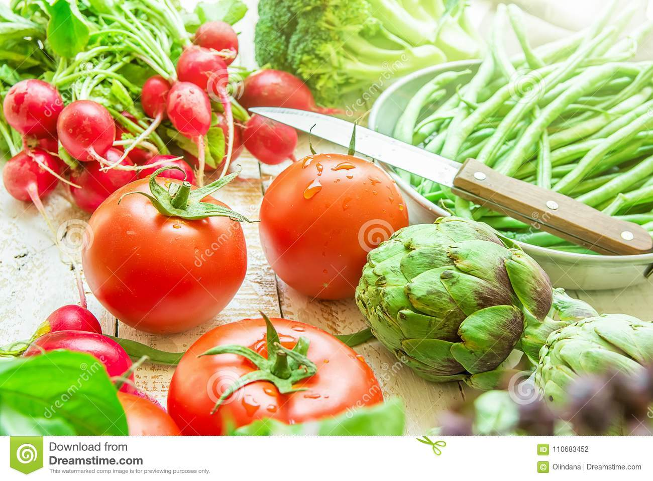 Variety of Fresh Organic Vegetables Artichokes Green Beans Tomatoes Red Radish Broccoli on Wood Garden Kitchen Table in Sunlight. Vegan Clean Eating ...