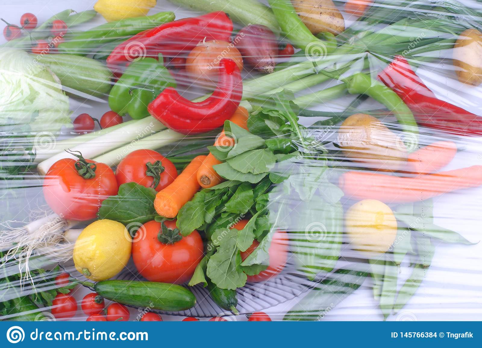 Variety of fresh raw organic fruits and vegetables in light brown containers sitting on bright blue wooden background
