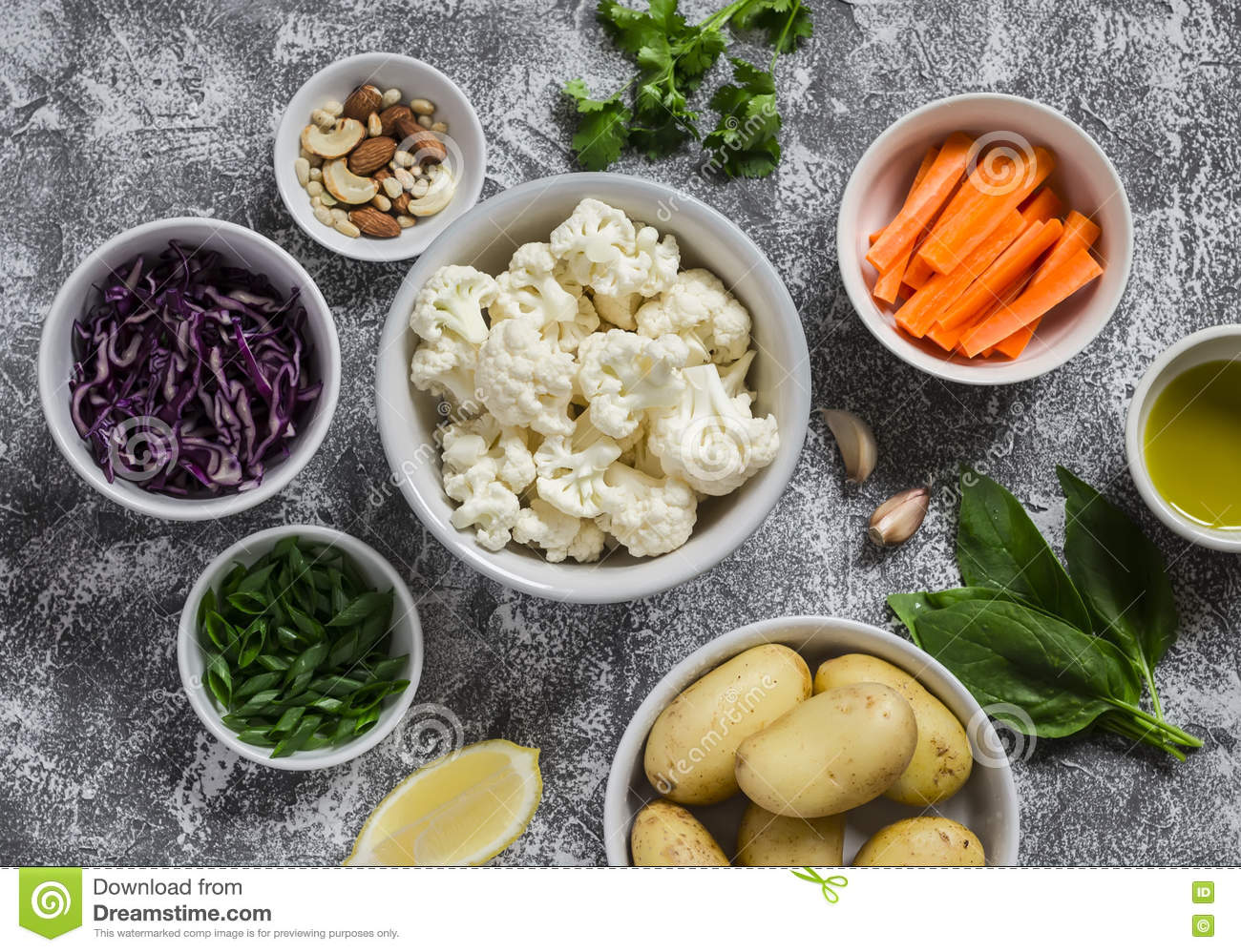 Variety of fresh vegetables in bowls - potatoes, red and cauliflower, spinach, green onions, carrots, nuts, olive oil, cilantro.