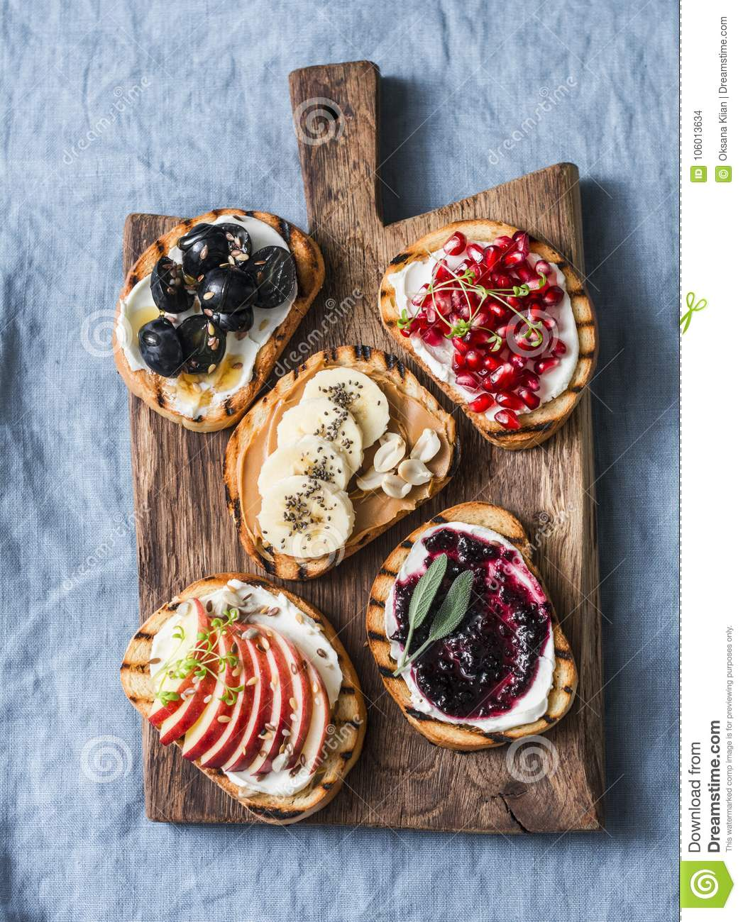 Variety grilled bread dessert sandwiches with cream cheese and apple, pomegranate, jam, grapes, peanut butter, banana, flax seed,