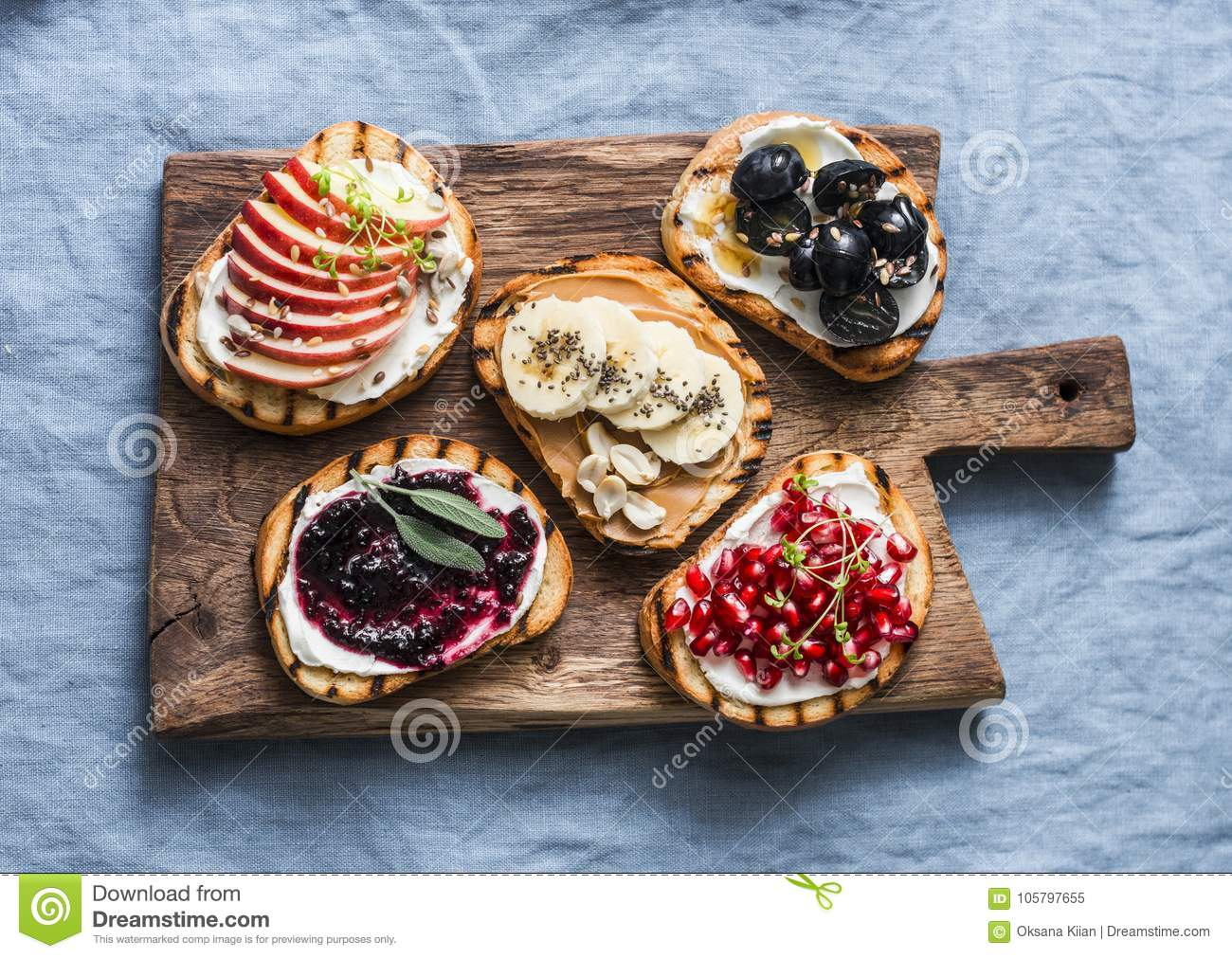 Variety grilled bread dessert small plates sandwiches with cream cheese and apple, pomegranate, jam, grapes, peanut butter, banana