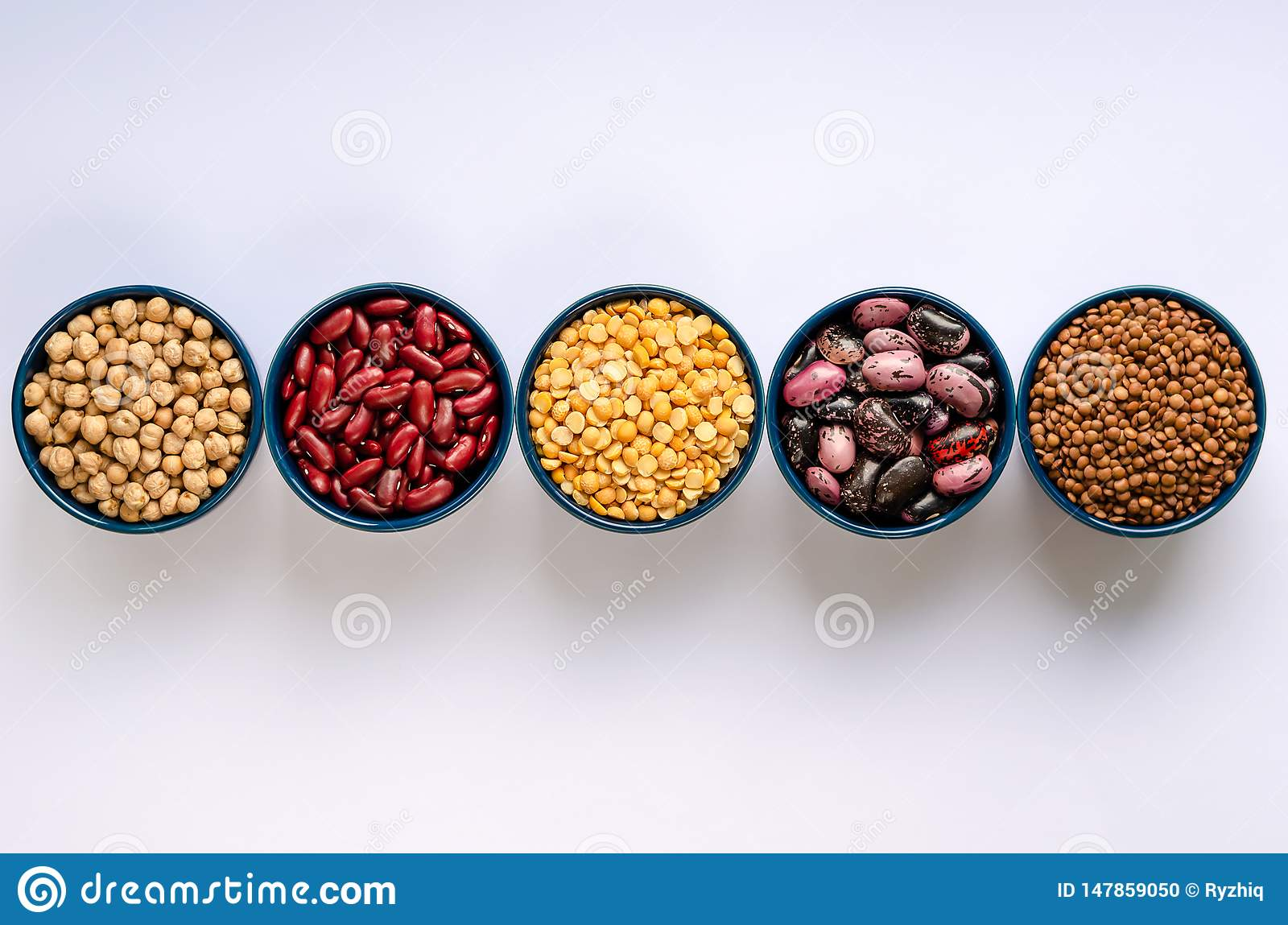 A variety of legumes. Lentils, chickpeas, peas and beans in blue bowls on a white background. Top view