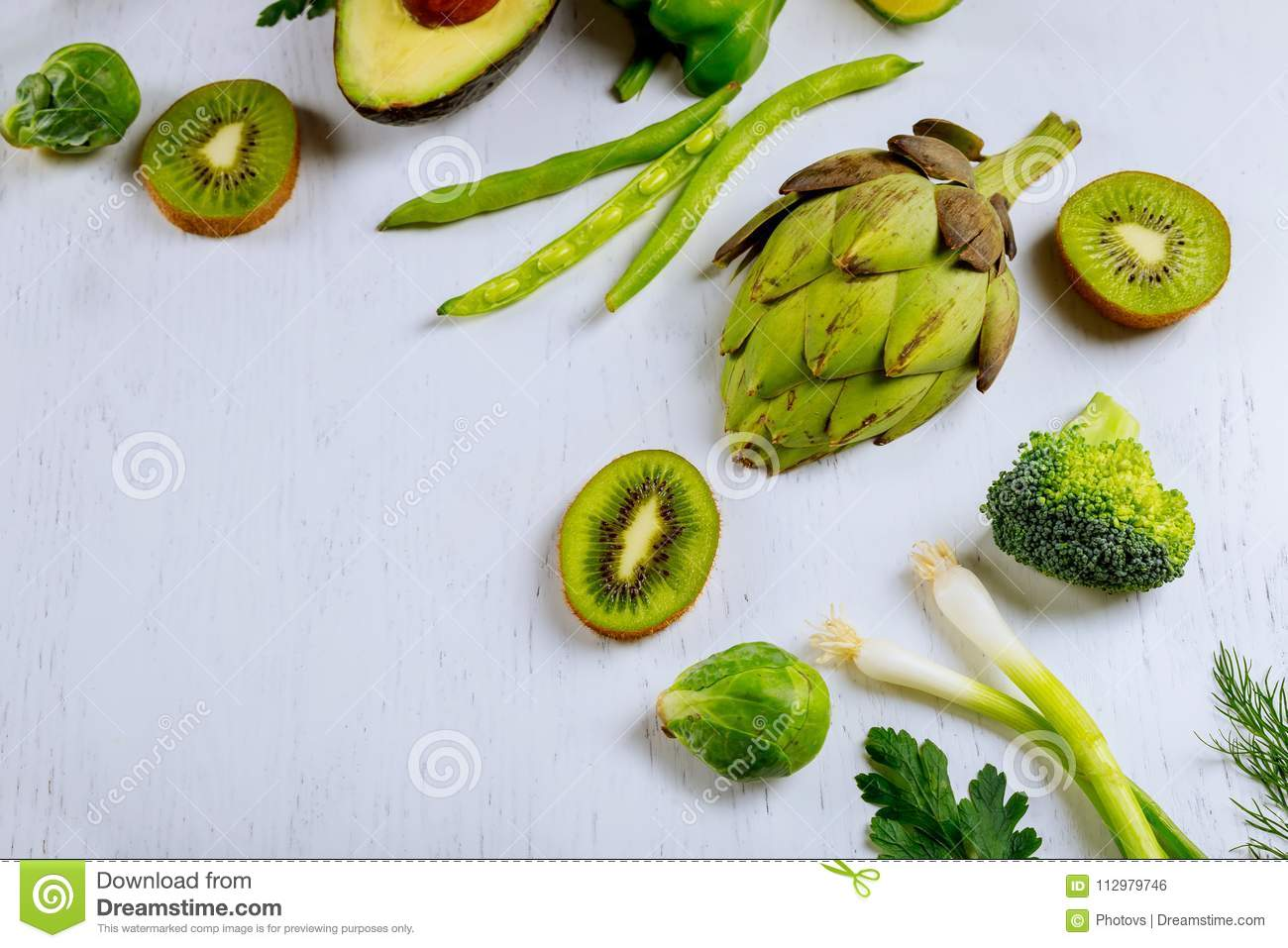 Variety of raw green vegetables salads, lettuce, bok choy, corn, broccoli, savoy cabbage as frame round empty white chopping board