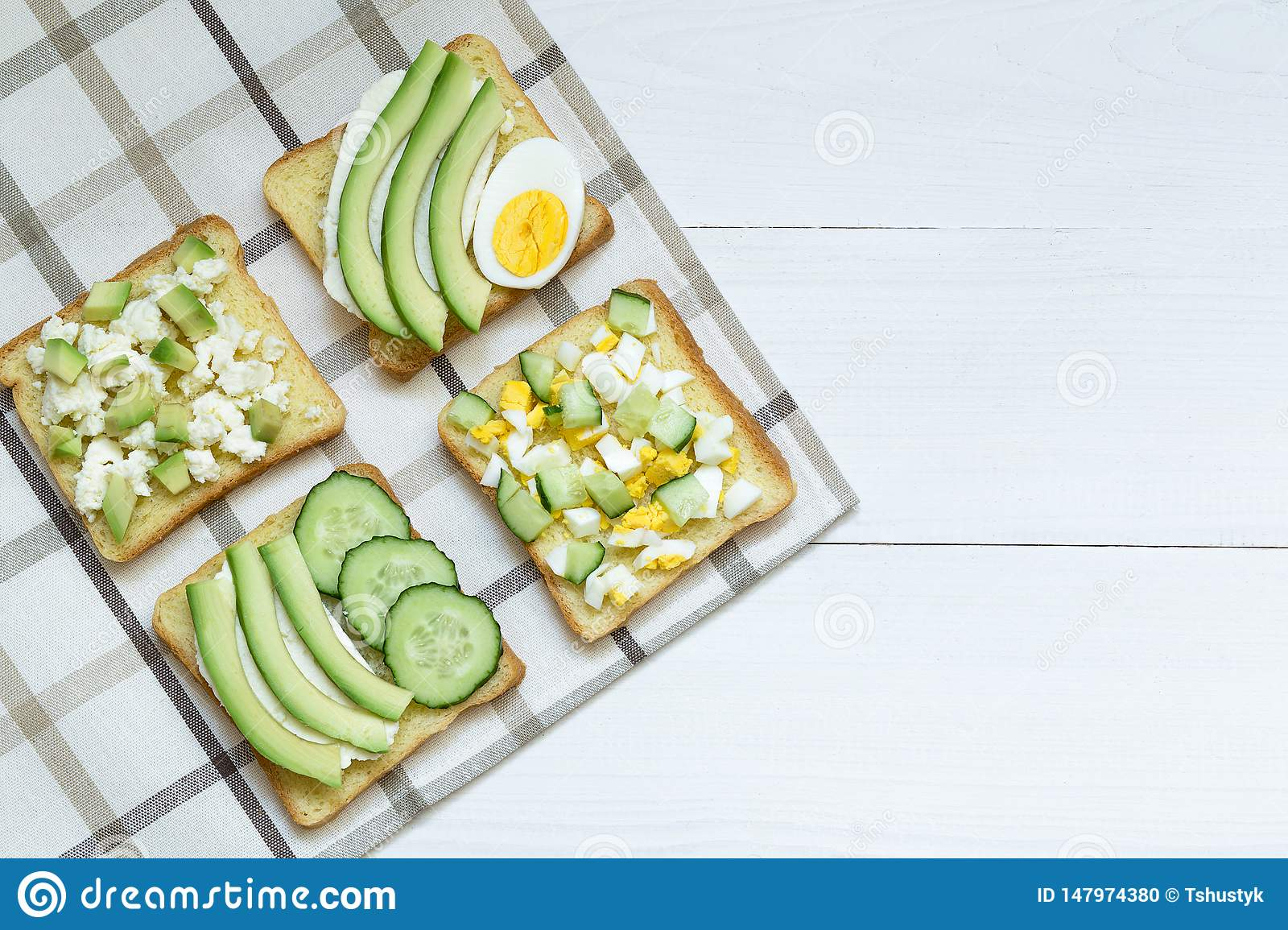 Variety of sandwiches for breakfast, snack, avocado, egg, cream cheese on bread sandwiches, white background
