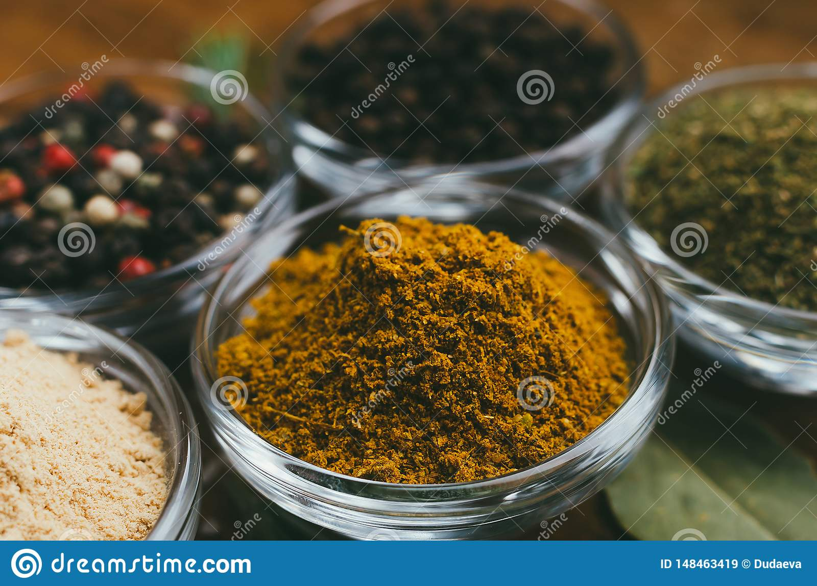 Variety of spices in round glass bowls - ground ginger, hops-suneli, kari, black pepper and mix