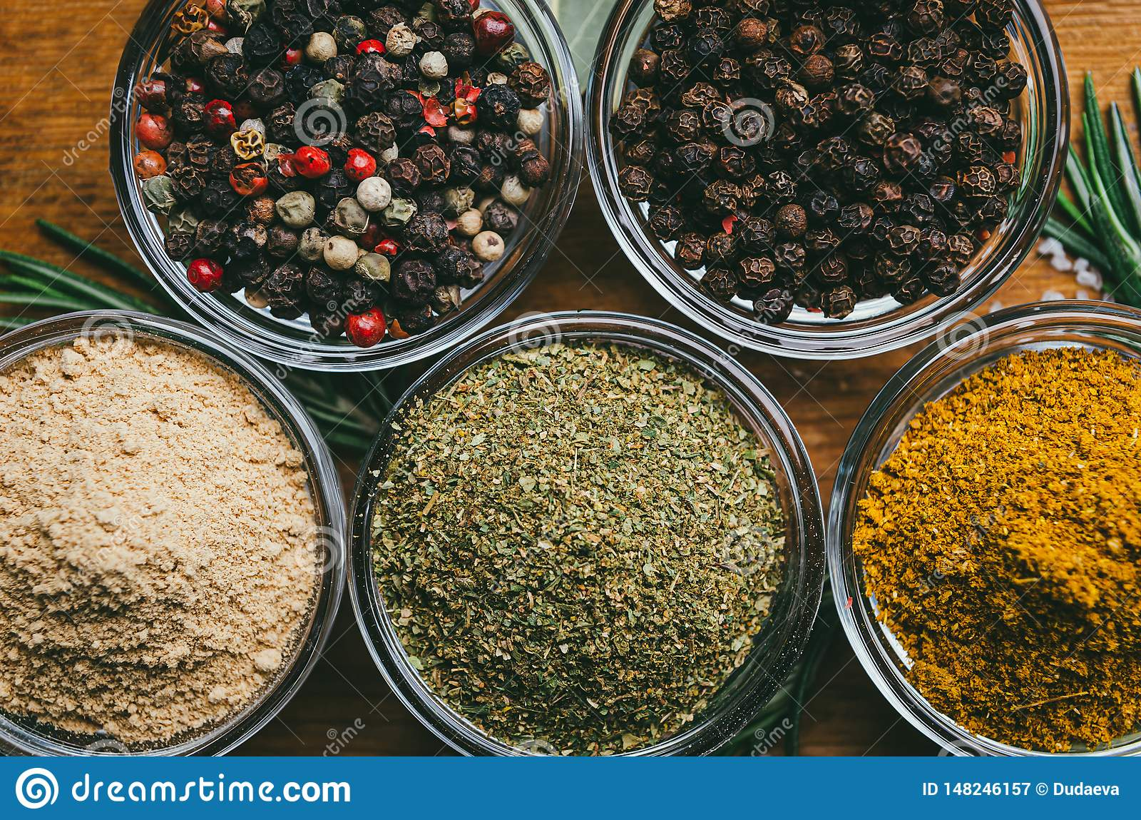 Variety of spices in round glass bowls - ground ginger, hops-suneli, kari, black pepper and a mixture