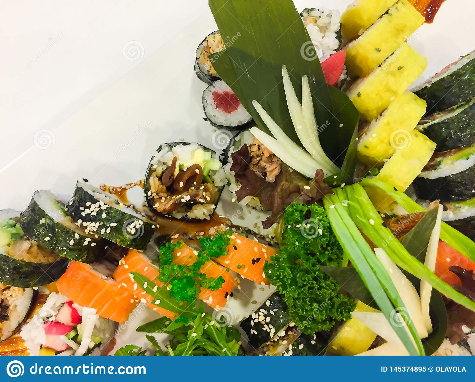 Variety of sushi rolls on a white plate