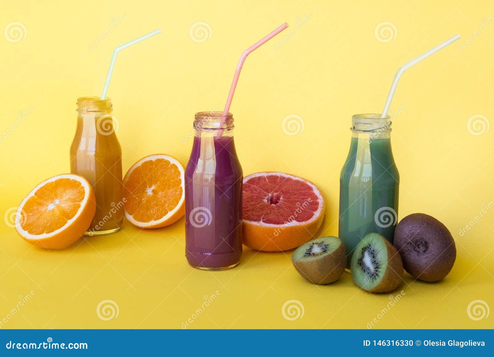 Vario genere di frullati o di succhi in bottiglie, concetto dell alimento di dieta sana su fondo giallo