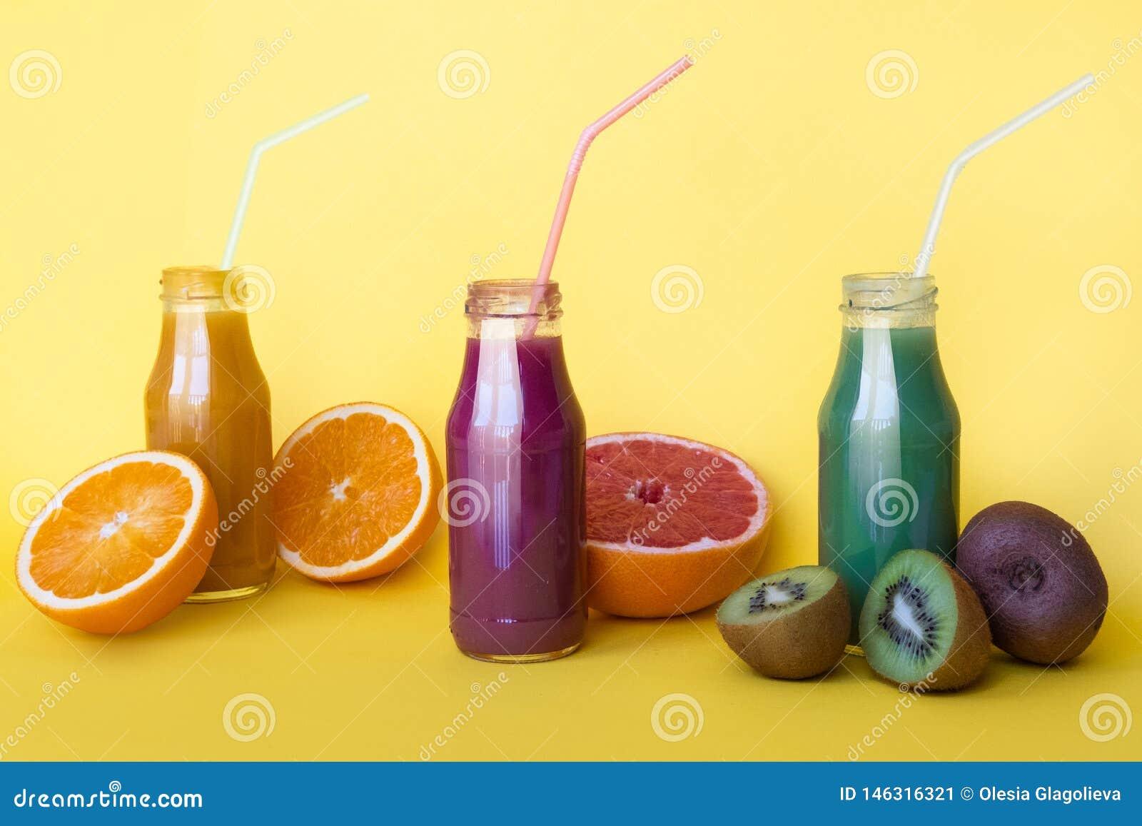 Vario genere di frullati o di succhi in bottiglie, concetto dell alimento di dieta sana su giallo