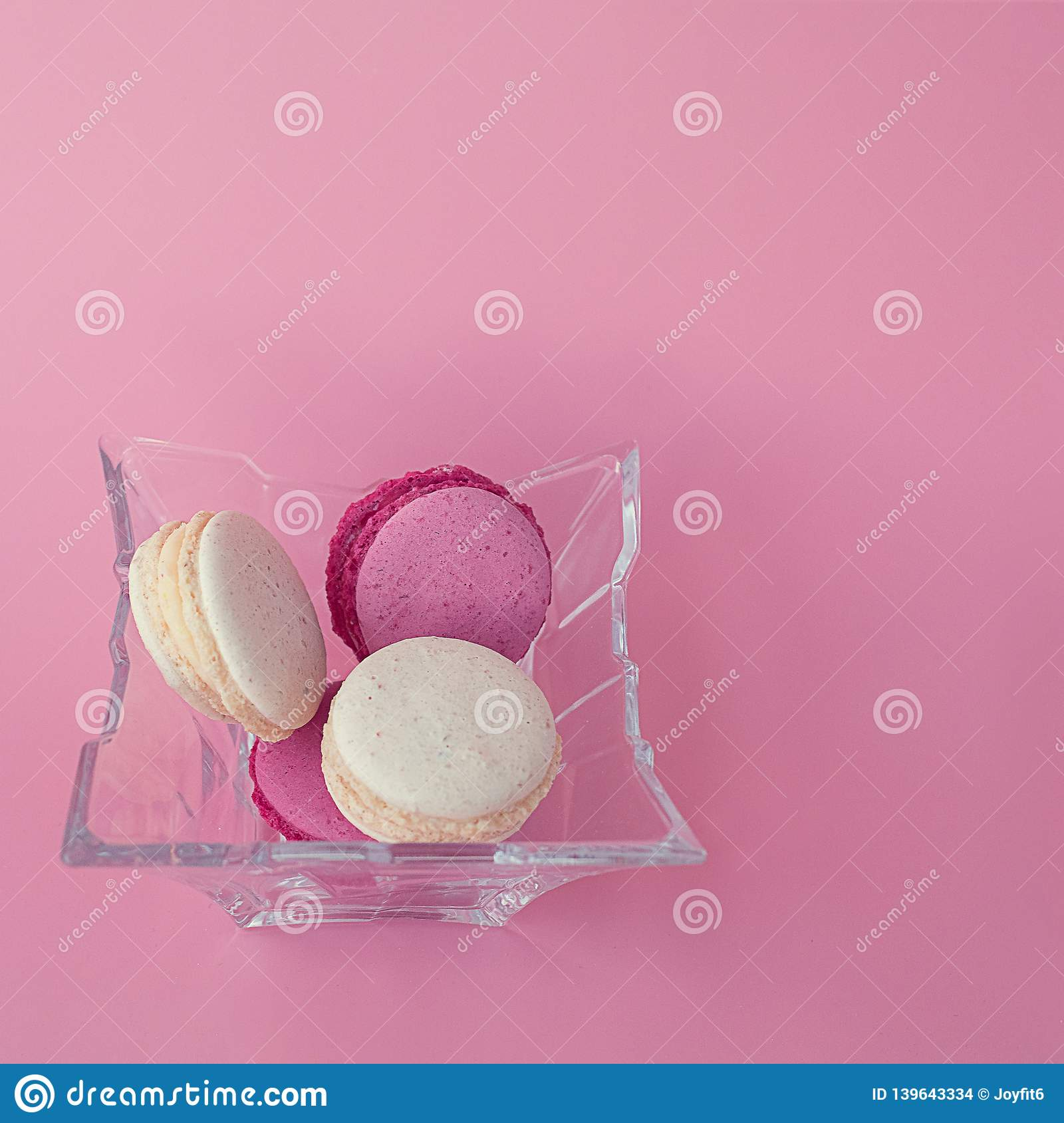Varios macarons multicolores en una placa de cristal en un fondo rosado cuadrado