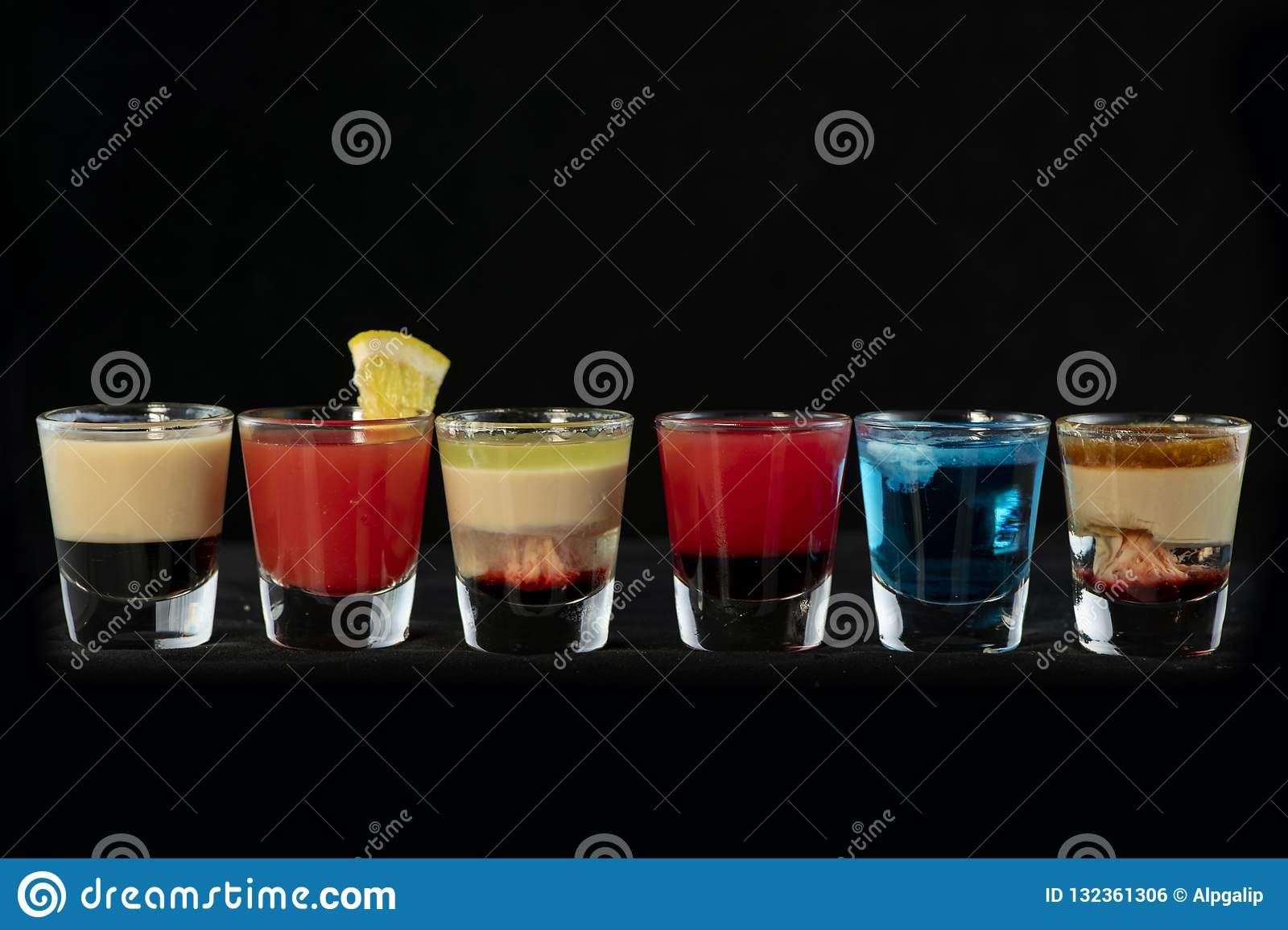 Mix alcoholic cocktail shots together with isolated black background