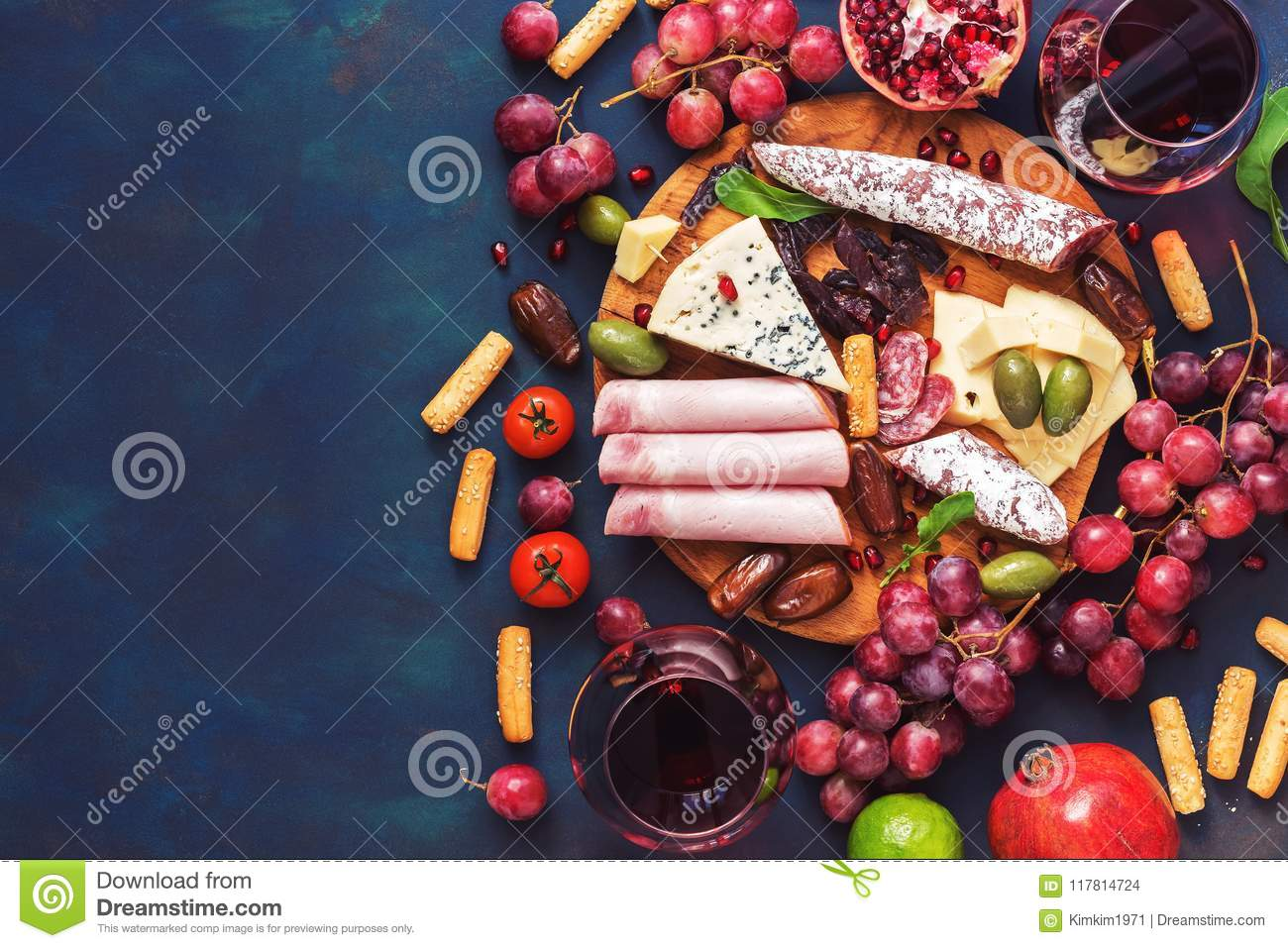 Various appetizer-red wine, fruits,sausages,cheese, vegetables on a dark finem background. Copy space, top view.