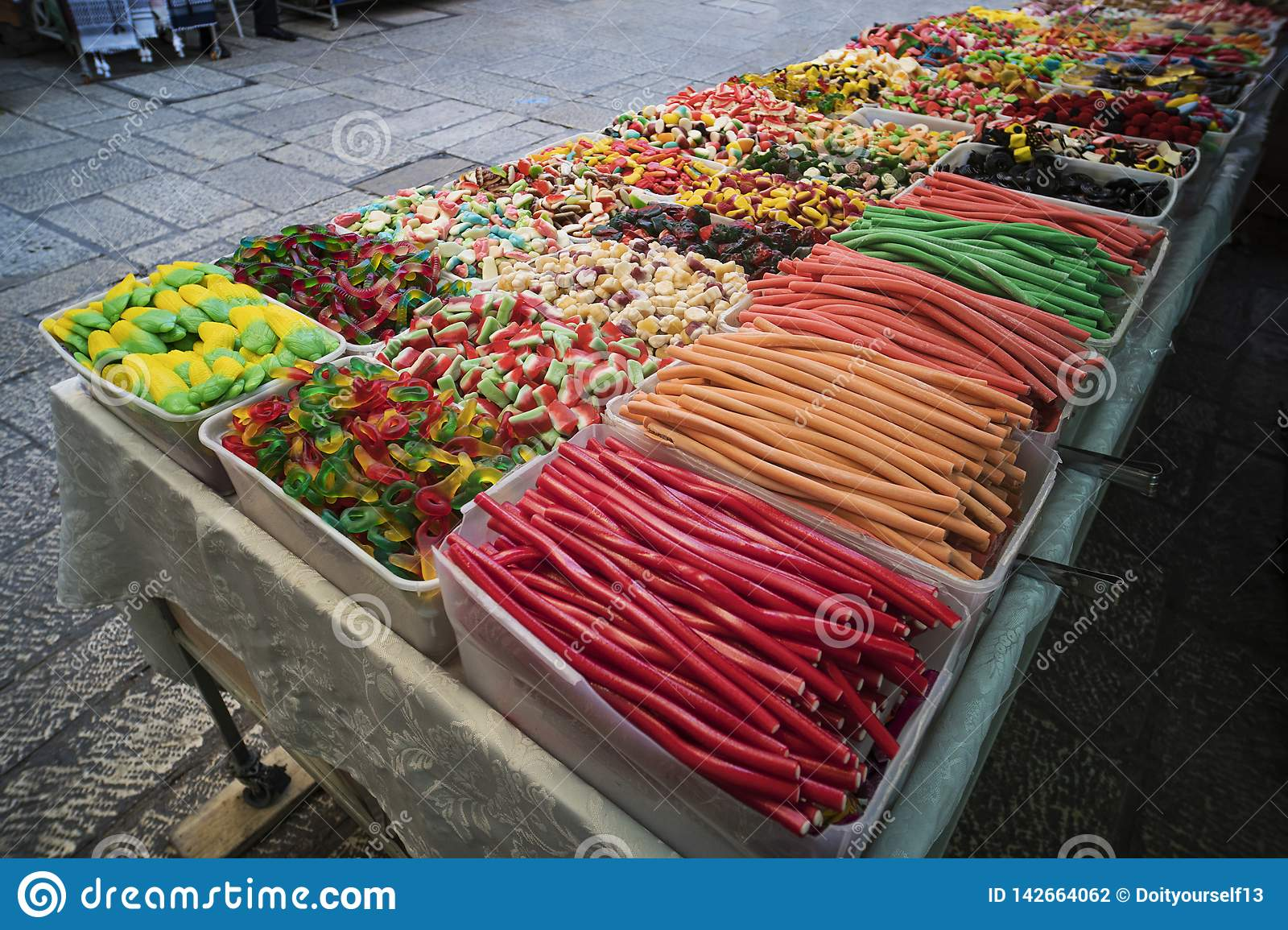 Various colorful jelly sweets and confectionary exposed in plastic boxes for sale in the street. Contrasting colors of candies and