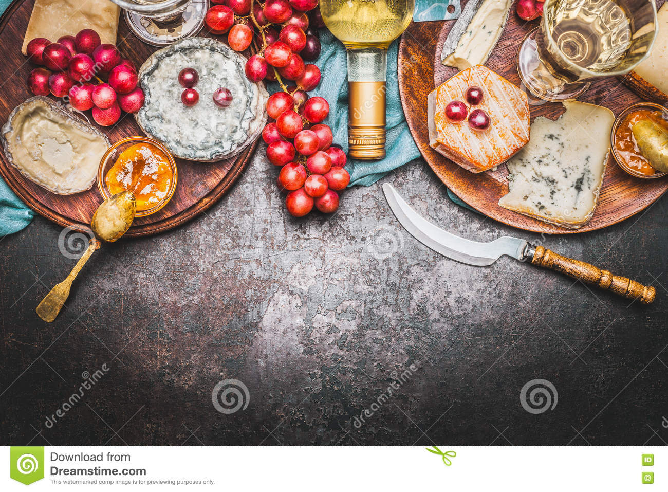 Various Fine cheese selection with Bottle of wine, Honey mustard sauce and grape on rustic background, top view