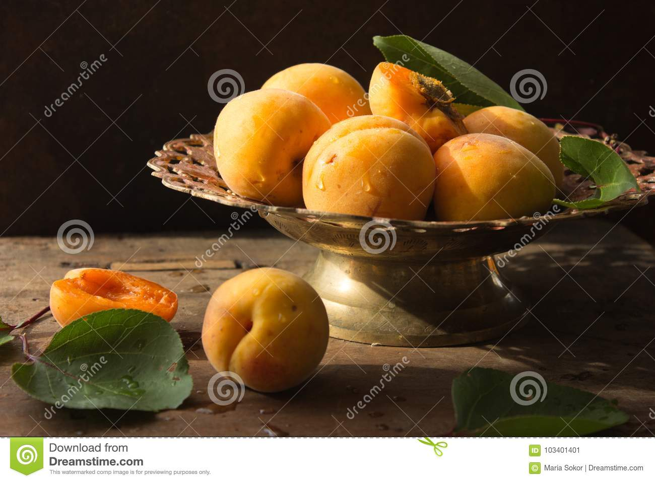 Various Fresh ripe apricots on wooden surface leaves fruits apricots on board cut apricots in half. Light blue rustic wood backgro