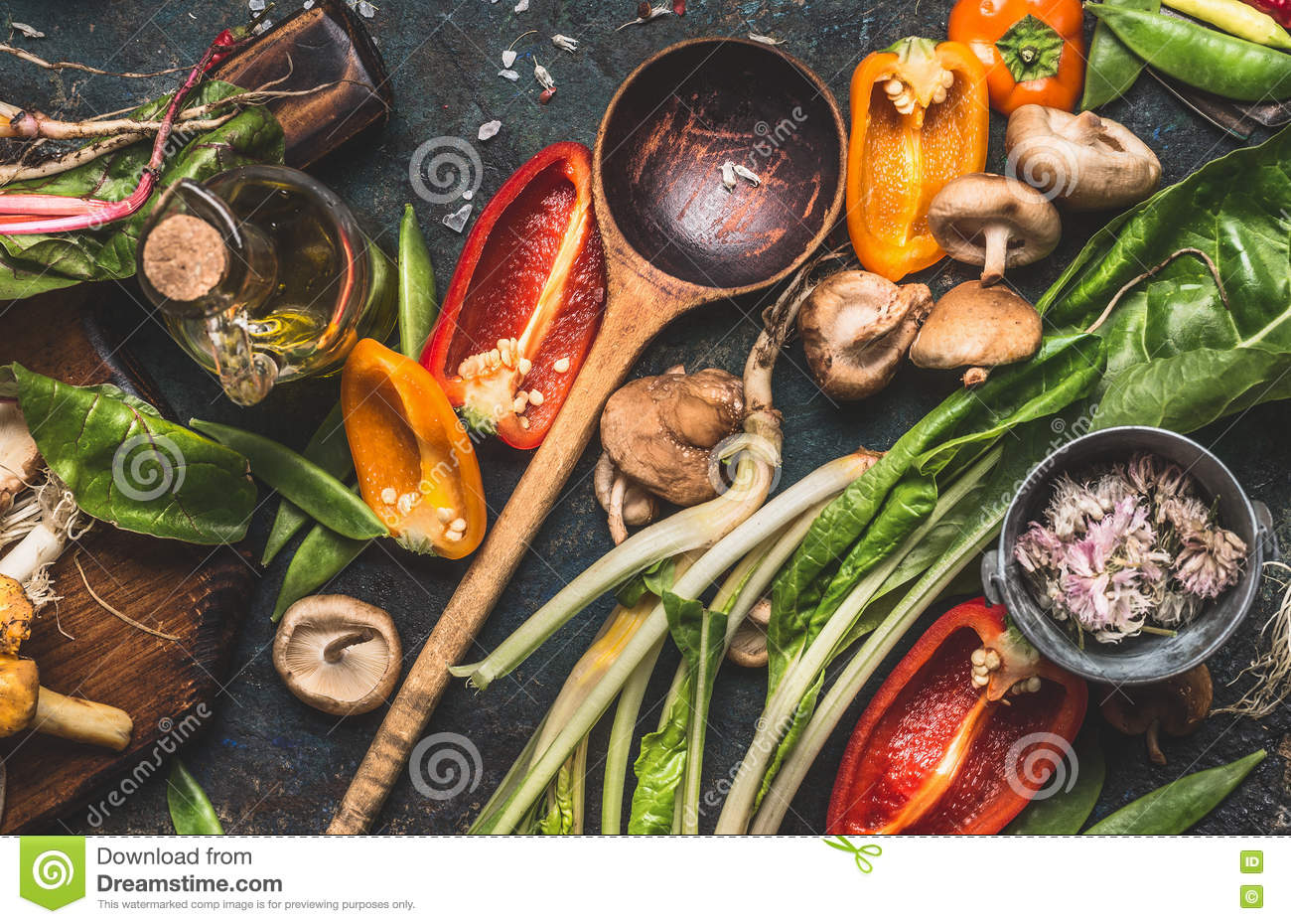 Various fresh vegetables with wooden cooking spoon for healthy eating and nutrition on dark rustic background