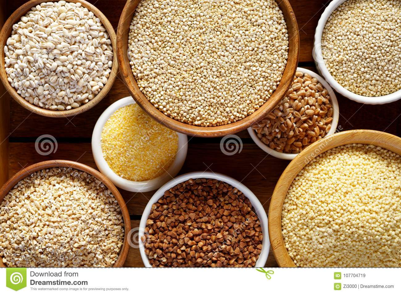 Various groats, cereals. Different types of groats in bowls on a wooden background, top view, close up.